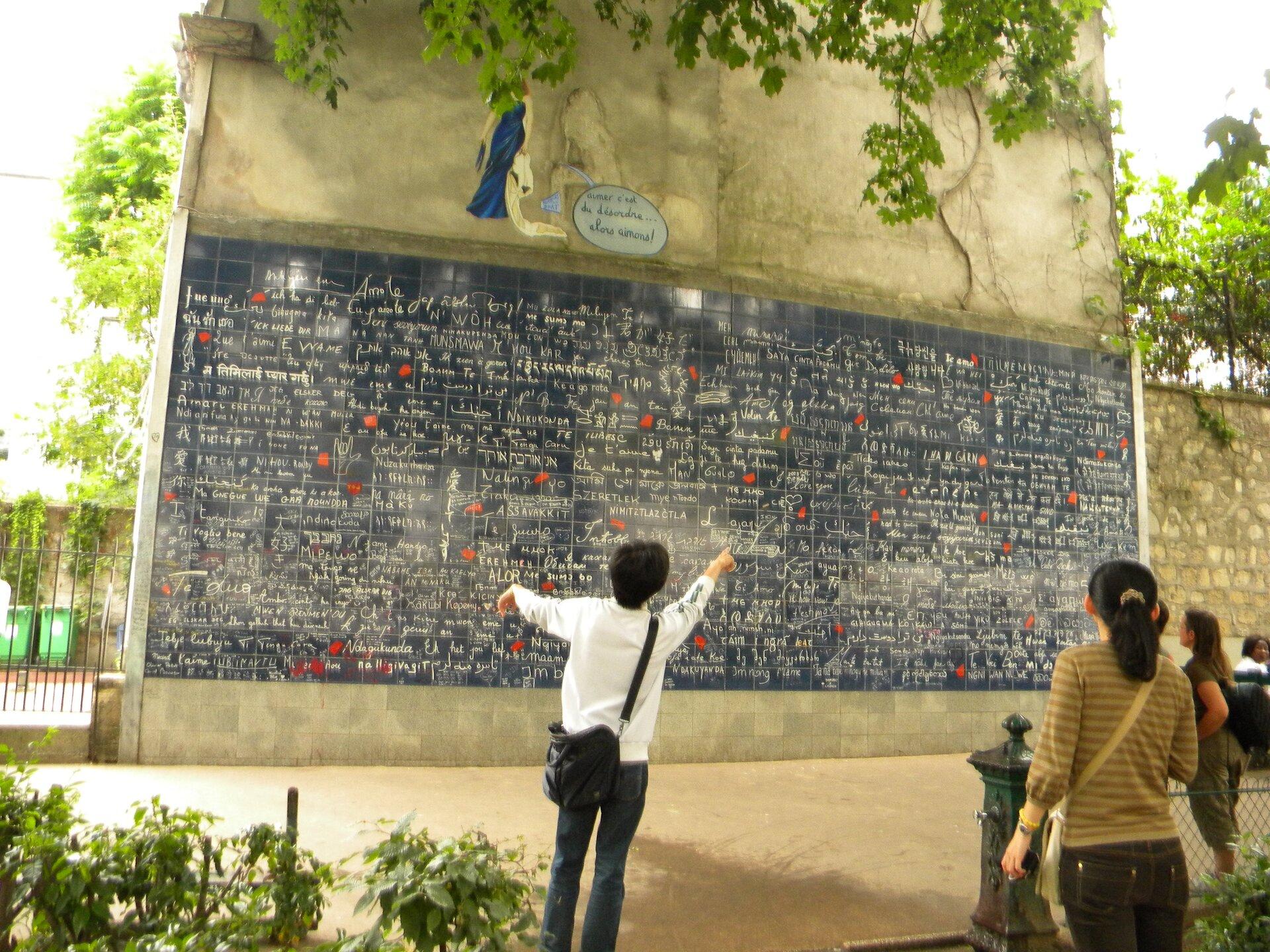 Na zdjęciu betonowa ściana zczarną tablicą zwielu płytek, białe napisy, przed ścianą kilka osób czyta napisy.