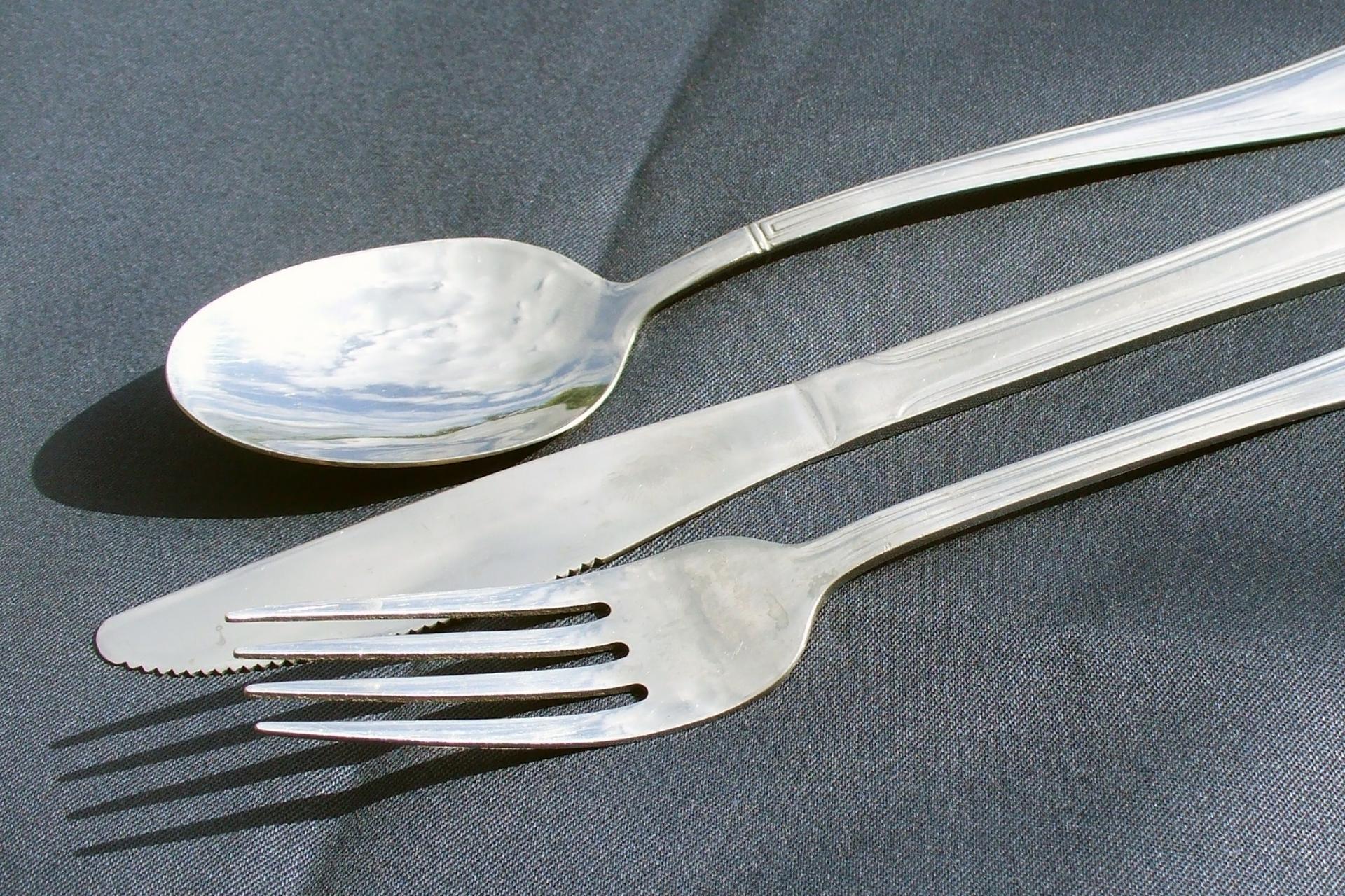Fotografia przedstawia metalowe sztućce: łyżkę, nóż iwidelec.