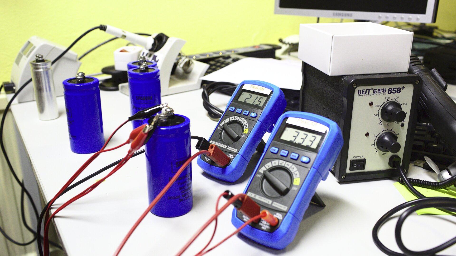 Zdjęcie przedstawia stół warsztatowy, którego użytkownik dokonuje operacji przywracania elementów elektronicznych zwanych kondensatorami, do pełnej sprawności. Kondensatory mają kształt dość dużych niebieskich cylindrów istoją obok siebie wliczbie czterech sztuk. Do jednego znich podłączone zostało źródło prądu oraz dwa multimetry mierzące napięcie przy obu zakończeniach, zwanych okładkami.