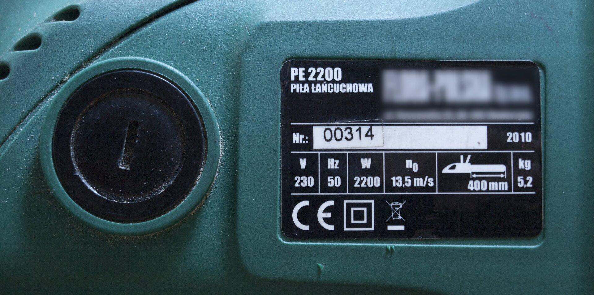 Zdjęcie przedstawia tabliczkę znamionową na obudowie elektrycznej piły łańcuchowej. Obudowa urządzenia zielona, po lewej stronie zdjęcia czarna zakrętka szczotki silnika używana podczas jej wymiany. Po prawej stronie czarna tabliczka zsymbolem towaru, typem (piła łańcuchowa), numerem seryjnym irokiem produkcji. Poniżej podstawowe parametry urządzenia: napięcie 230 woltów, 50 herców, moc 2200 watów, prędkość przesuwu łańcucha 13,5 metra na sekundę, długość prowadnicy 400 milimetrów, masa 5,2 kilograma.