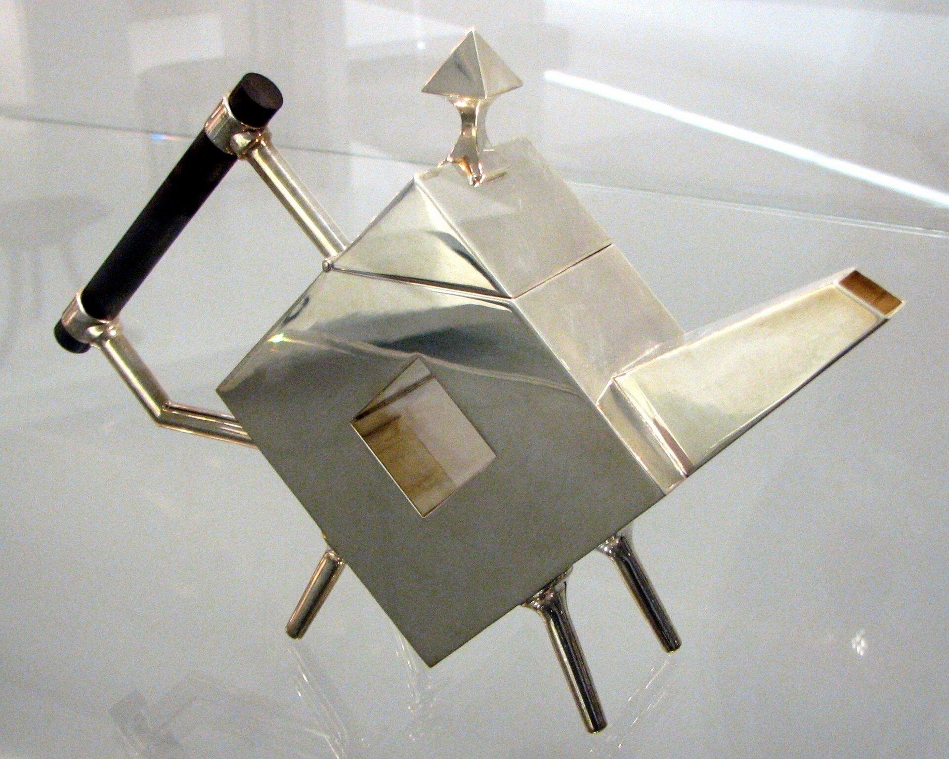 Ilustracja przedstawia czajniczek zaprojektowany prez Christophera Dressera. Naczynie posiada niecodzienną kańciastą formę, cechują go geometryczne złote kształty. Projektant starał się uchwycić funkcjonalność rzeczy codziennego użytku wraz zniecodziennym kształtem.