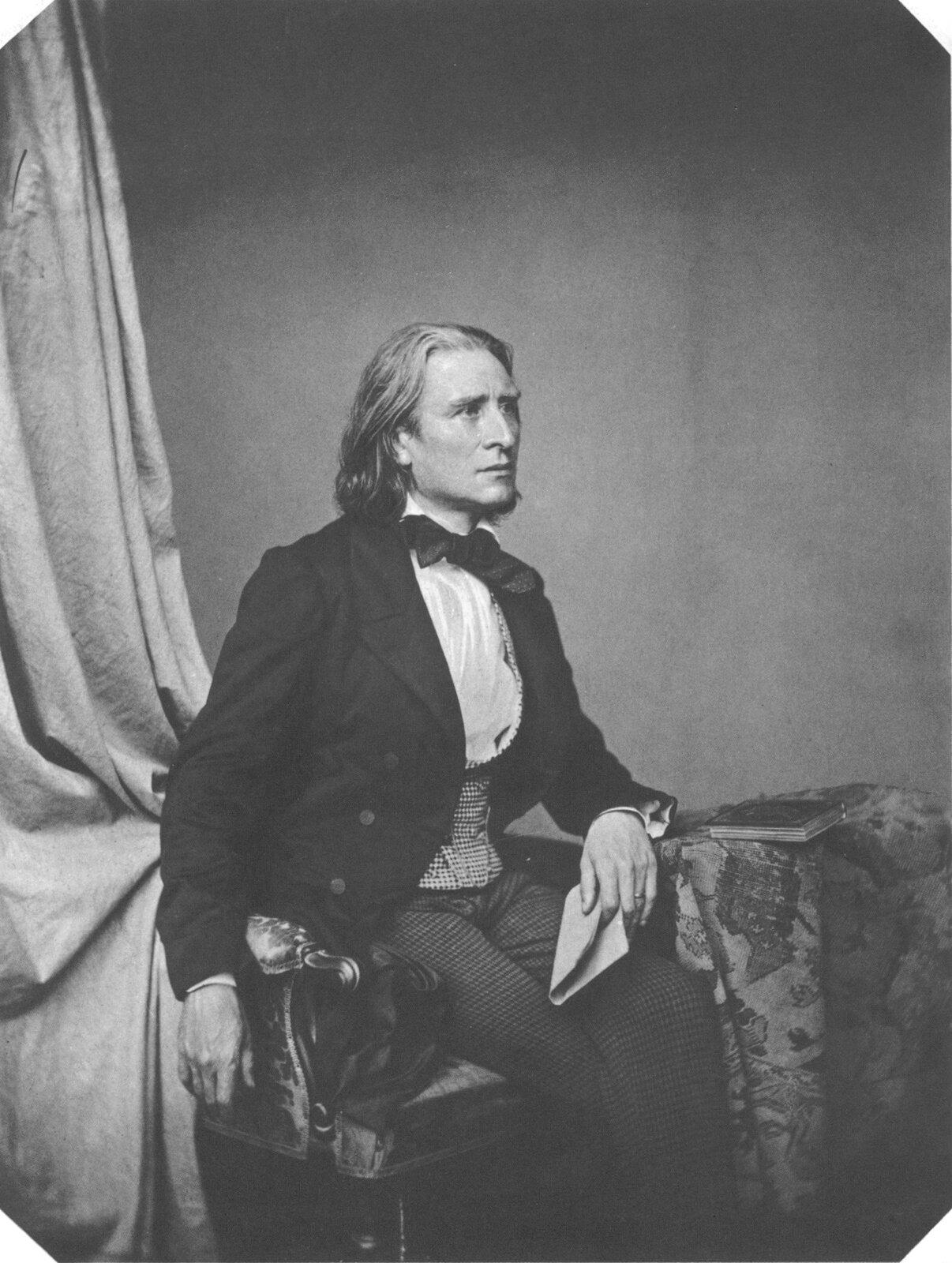 Fotografia przedstawia portret Franciszka Liszta. Mężczyzna patrzy przed siebie, siedzi na pięknie zdobionym krześle, ma długie włosy ispokojny wyraz twarzy.