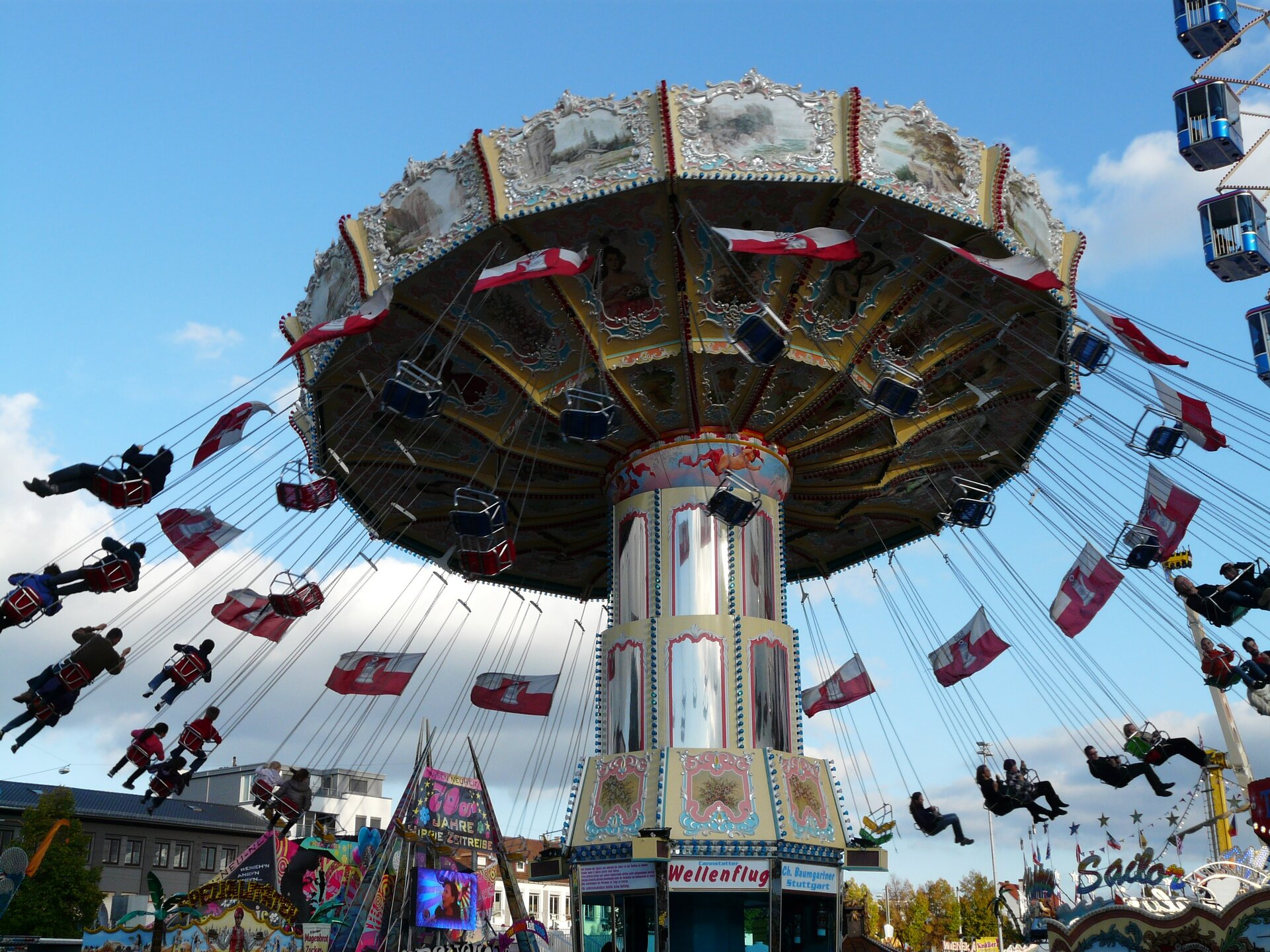 Zdjęcie przedstawia dużą karuzelę łańcuchową. Na karuzeli znajduje się kilkanaście osób. Wtle błękitne niebo.