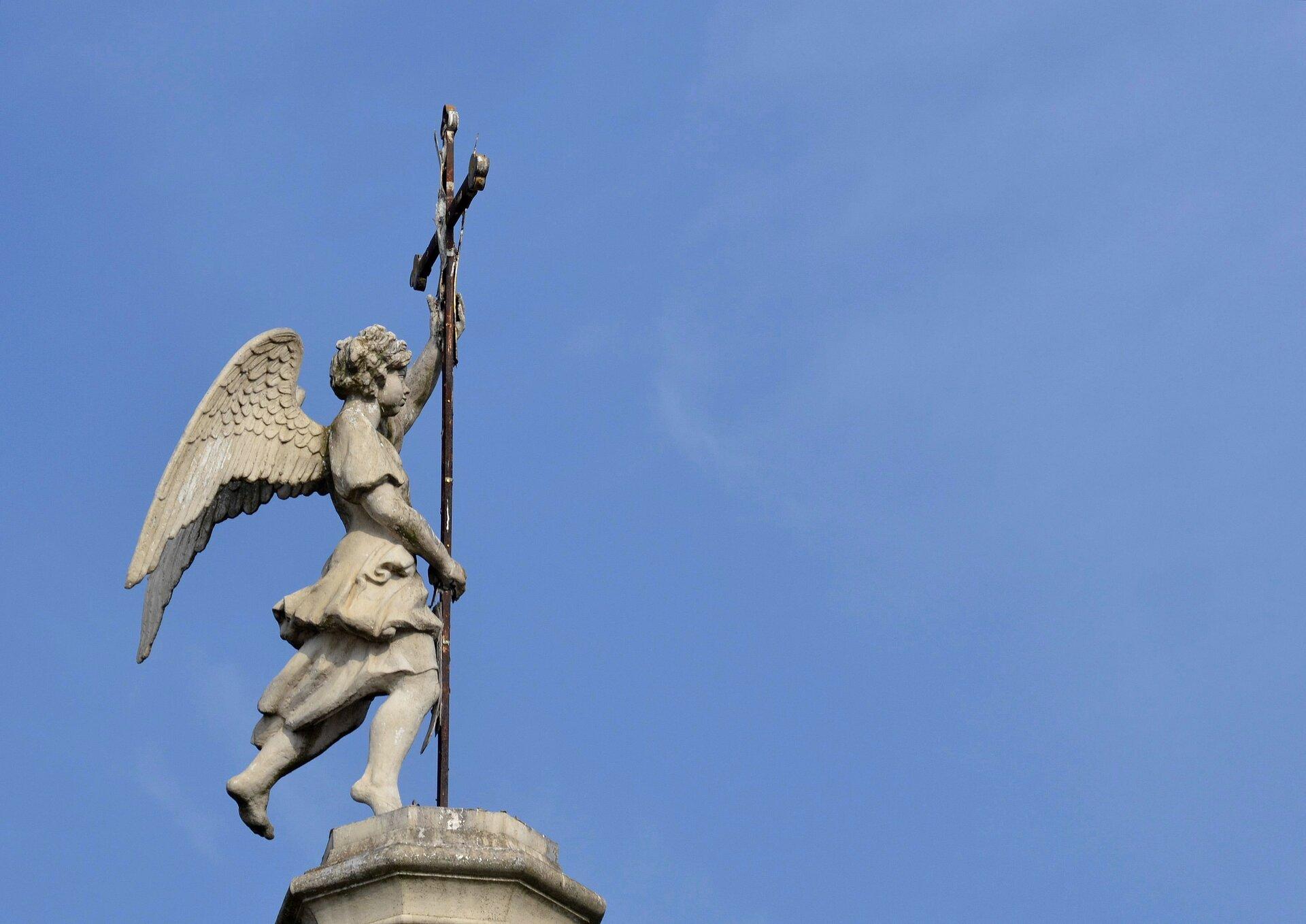 Ilustracja przedstawia rzeźbę zkościoła Merciful Saviour zXVIII w. Na zdjęciu znajduje się rzeźba anioła ustawionego na dachu wierzy budowli. Ubrana wpowłóczyste szaty postać ze skrzydłami, rękoma przytrzymuje się metalowego krzyża. Stoi na jednej nodze, druga uniesiona jest lekko do tyłu. Kamienny posąg, ukazany na tle niebieskiego nieba, skierowany jest wprawą stronę.