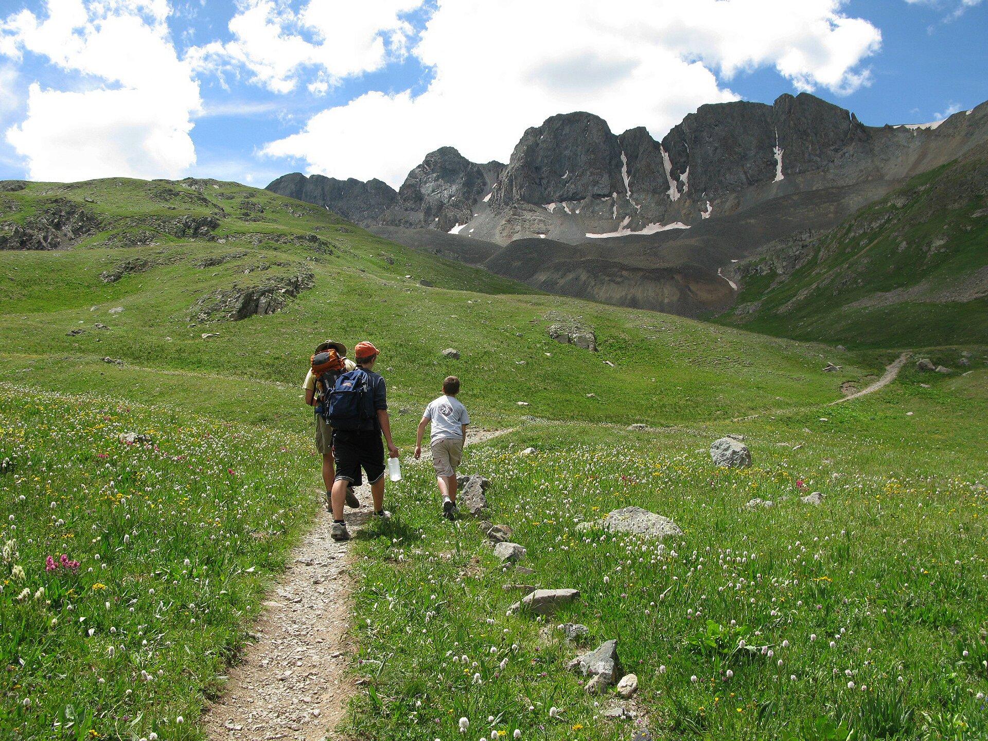 Fotografia przedstawia trzyosobową grupę ludzi, chłopca idwie starsze osoby, wędrujących po ścieżce wgórach. Każda ze starszych osób niesie plecak, ajedna znich dodatkowo butelkę zwodą. Zejście ścieżką jest łagodne, ale przed wędrowcami widać wysokie, skaliste góry.