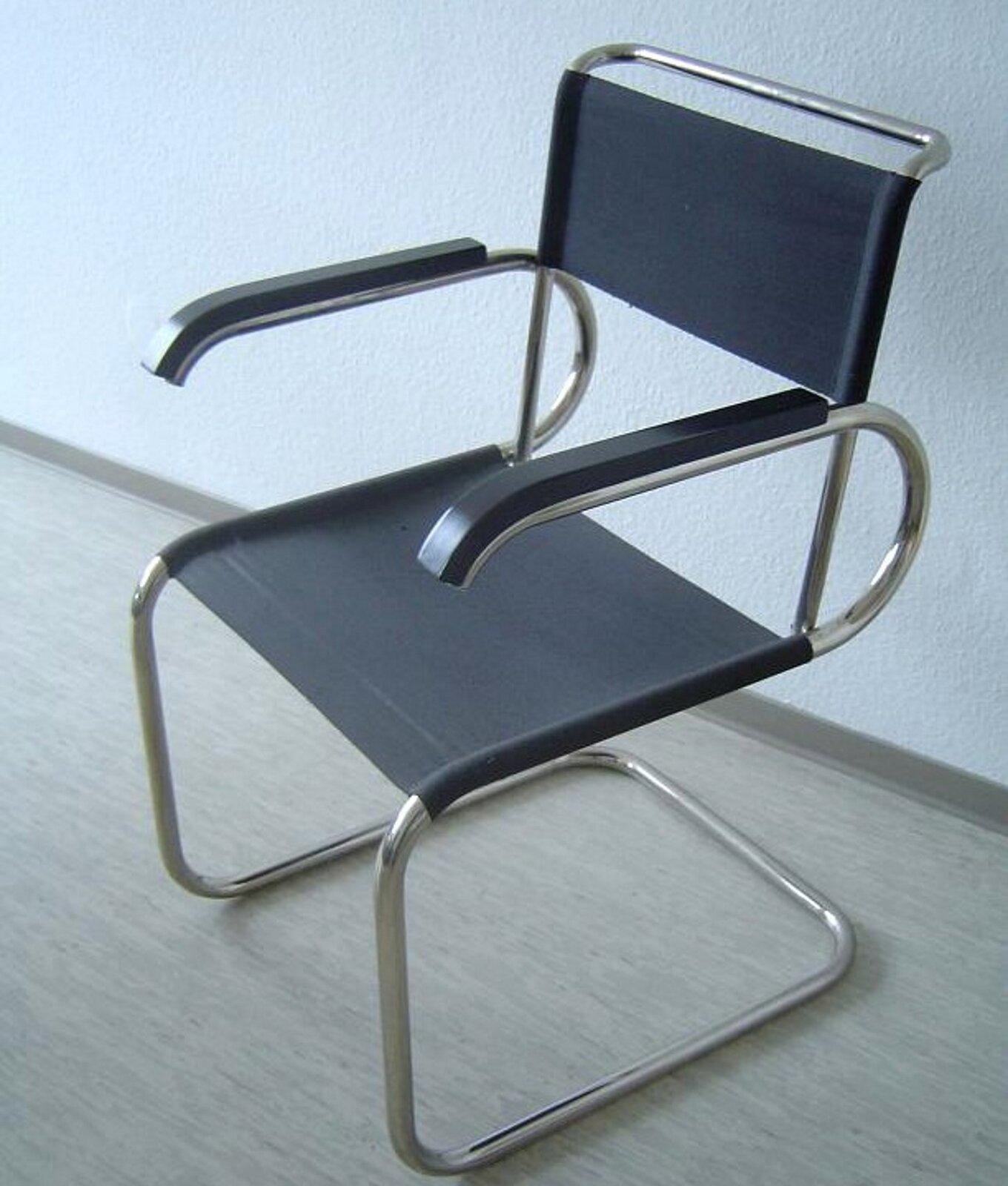 Ilustracja przedstawia krzesło zawieszone, zaprojektowane przez Marcela Breuera. Mebel posiada prosty kształt, cechuje go funkcjonalnośc bez zbędnych ozdób. Posiada stalową konkstrukcję igranatowe oparcie wraz zsiedziskiem. Krzesło tego rodzaju jest nierzadko spotykane do dziś.
