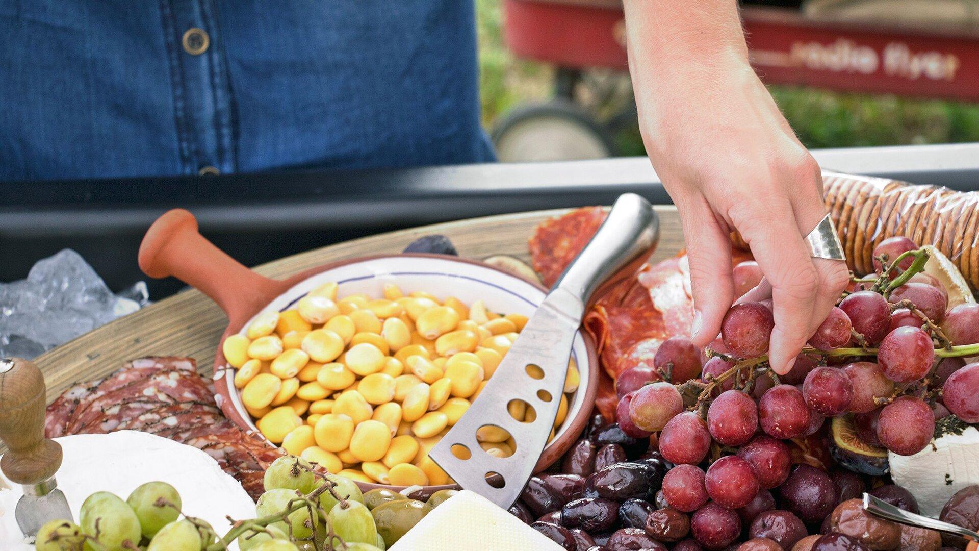 Ilustracja przedstawia zdjęcie osoby stojącej przy stole. Przedstawiona osoba ubrana jest wciemnoniebieską koszulę. Widać tylko fragment tułowia ilewą dłoń zpierścionkiem na środkowym palcu. Dłoń sięga po leżące na stole czerwone winogrono. Na stole leżą inne produkty żywnościowe oróżnej kaloryczności: białe winogrono, daktyle, zapakowane wfolię ciastka, pokrojona wplastry wędlina oraz żółte ziarna (prawdopodobnie fasola).