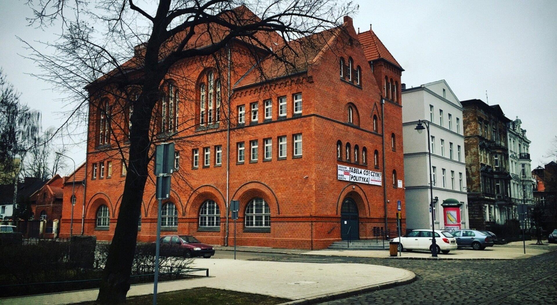 """Ilustracja przedstawia Centrum Nauki Współczesnej """"Łaźnia"""" wGdańsku. Na zdjęciu ukazany jest wysoki budynek, na planie prostokąta zczerwonej cegły. Na parterze znajduje się pięć dużych okien oraz dwuskrzydłowe drzwi. Zarówno drzwi jak iokna zwieńczone są łukami. Nad parterowymi oknami umieszczono rząd małych, prostokątnych okienek, nad którymi wznoszą się kolejne wysokie na dwie kondygnacje, trójdzielne okna zwieńczone łukiem. We frontowej części budowli, nad drzwiami znajdują się trzy rzędy łukowatych okienek. Bryła Centrum przykryta jest kilkoma czerwonymi dachami zceramiczną dachówką. Budynek ustawiony jest wprzestrzeni miejskiej. Za budowlą znajduje się rząd kamieniczek, natomiast przed nią wybrukowana szarą kostką uliczka."""