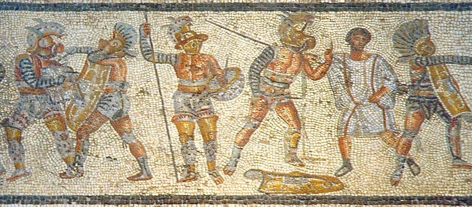 Ilustracja przedstawia rzymskich gladiatorów. Dzieło ukazuje sceny zczasu walki wojowników. Gladiatorzy są opancerzani od stóp do głów. Osłaniały ich hełmy ozdobione wielkim grzebieniem ipiórami oraz metalowe nagolenniki. Wojownicy wyposażeni byli we włócznię oraz okrągłą lub podłużną tarczę. Mozaika wykończona jest czarno-białą geometryczną granicą.