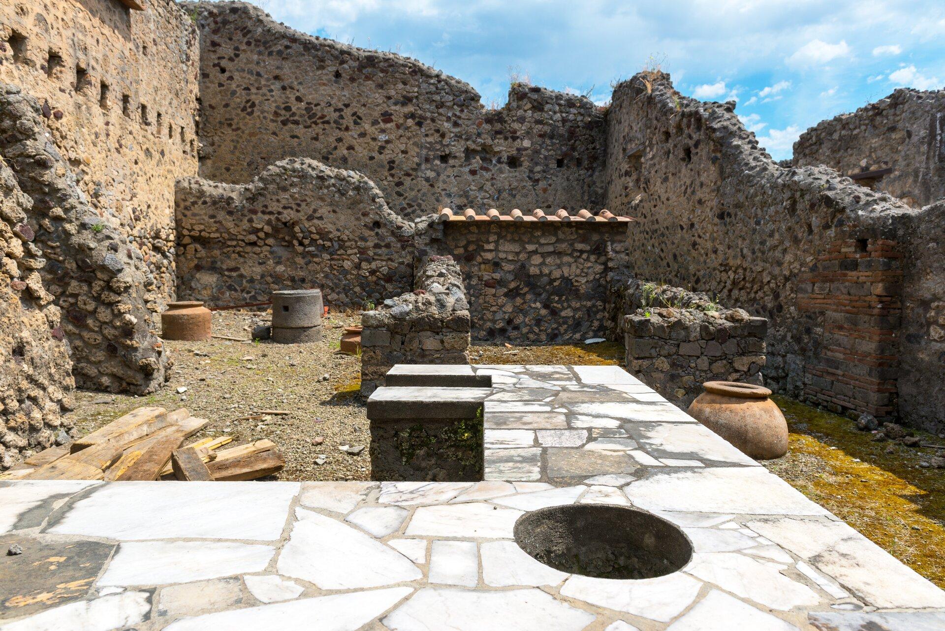 Kolorowa ilustracja przedstawia wnętrze starożytnej jadalni domu wPompejach. Na szerokim kamiennym blacie znajduje się wydrążony okrągły otwór. Nieopodal stoją duże gliniane kadzie. Zmurów domu pozostały ruiny.