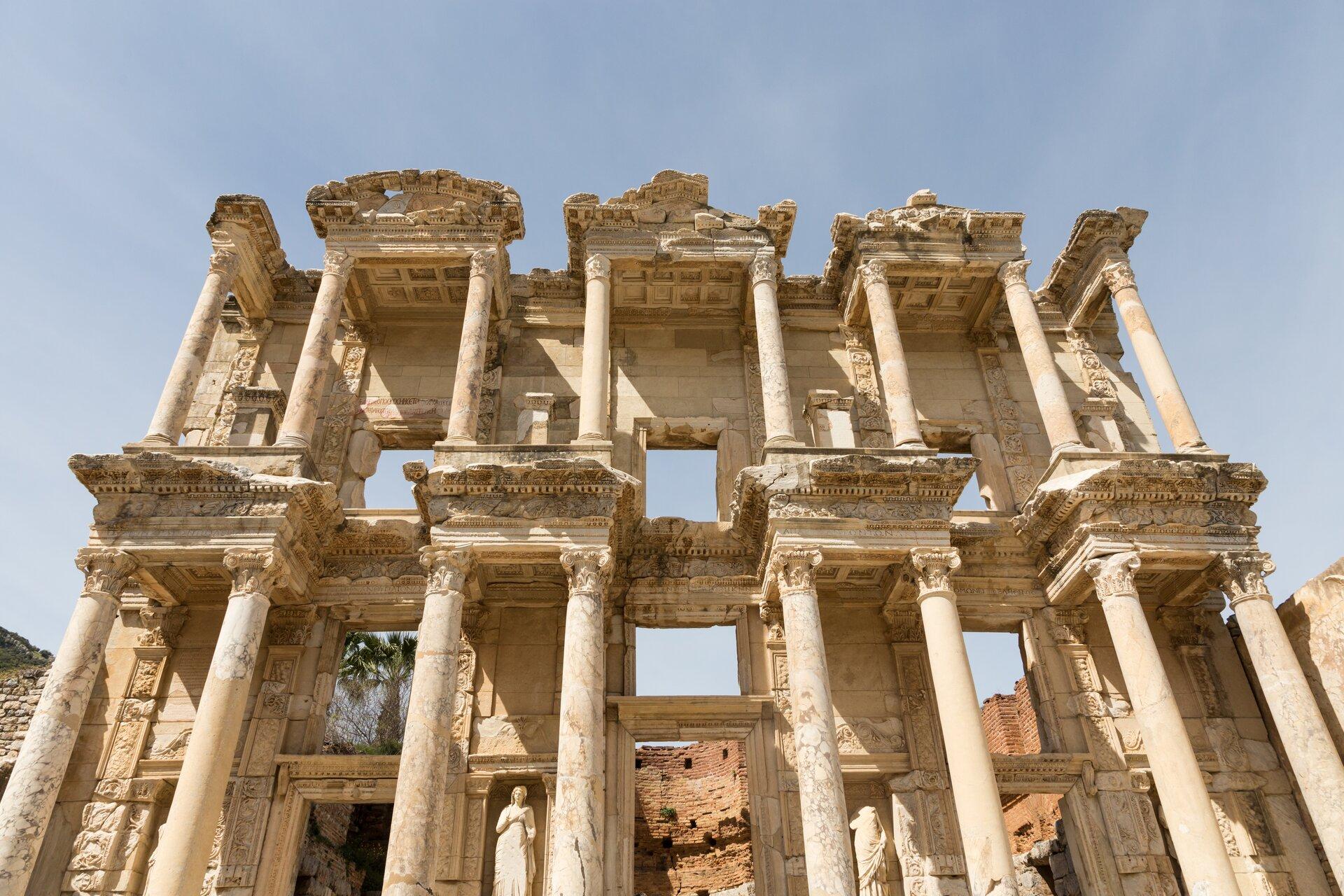 Fotografia nieznanego autora przedstawia ruiny starożytnej budowli Biblioteki Hadriana. Budynek składa się ze ścian oraz zkolumnady. Na samym dole pomiędzy kolumnami widoczne są rzeźby przedstawiające kobiety.  Wtle za ruinami znajdują się brązowe mury.