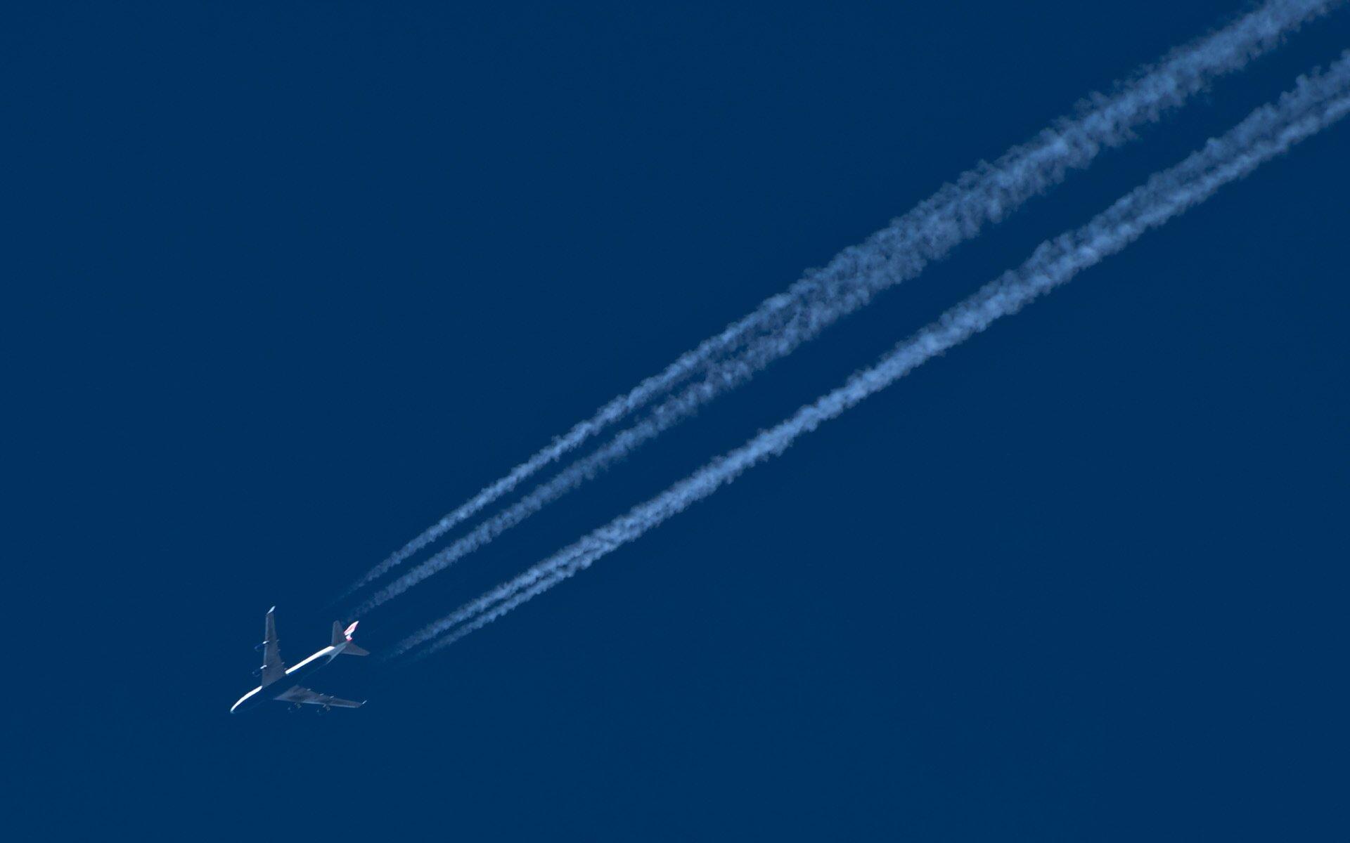 Zdjęcie przedstawia lecący samolot. Tłem jest niebieskie niebo. Samolot piały. Za samolotem widoczne białe linie przypominające chmury. Linie zaznaczają tor ruchu, po którym poruszał się samolot.