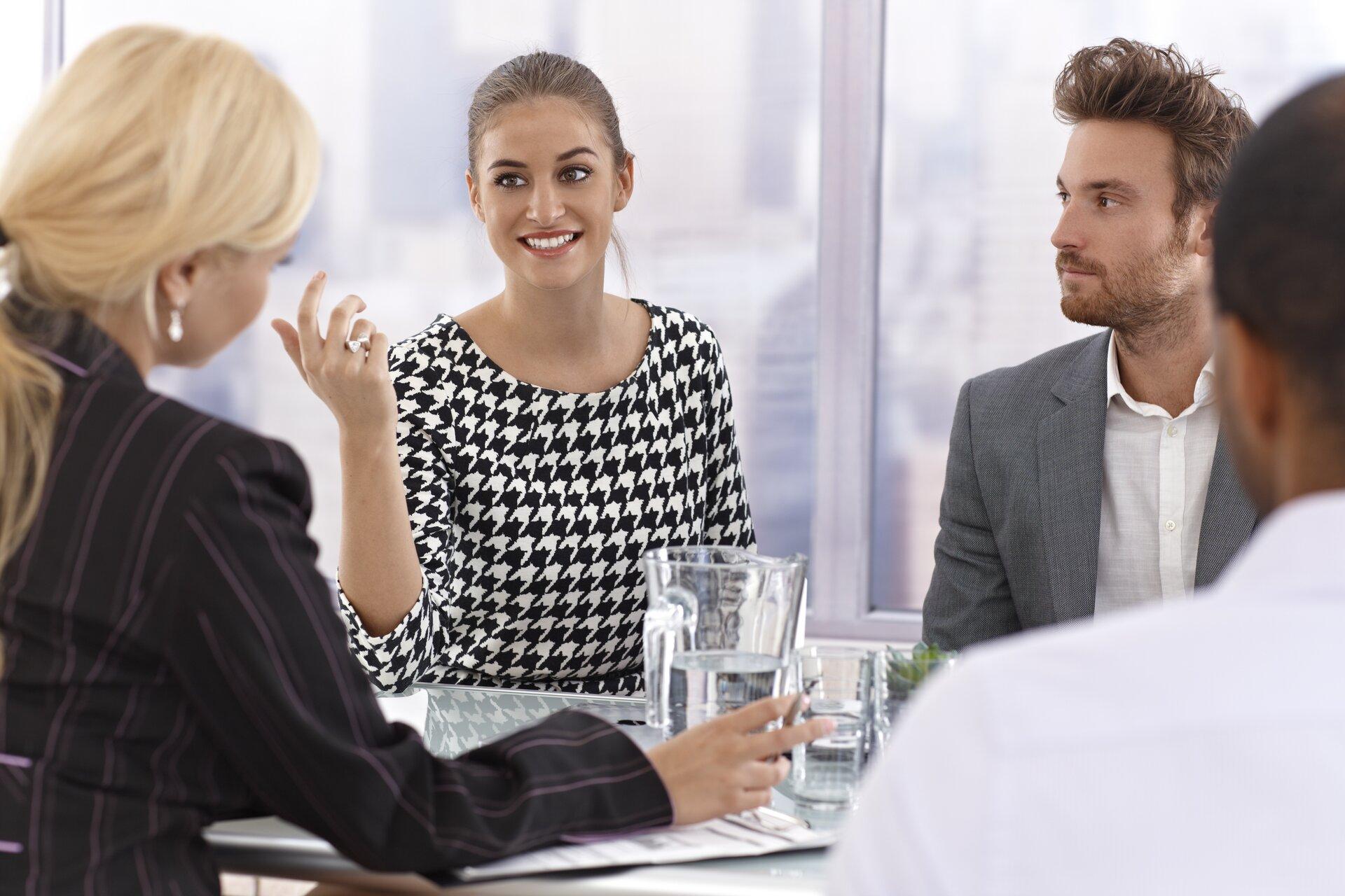Ilustracja przedstawia grupę ludzi rozmawiających podczas spotkania biznesowego. Przy stole siedzą dwie kobiety idwóch mężczyzn.