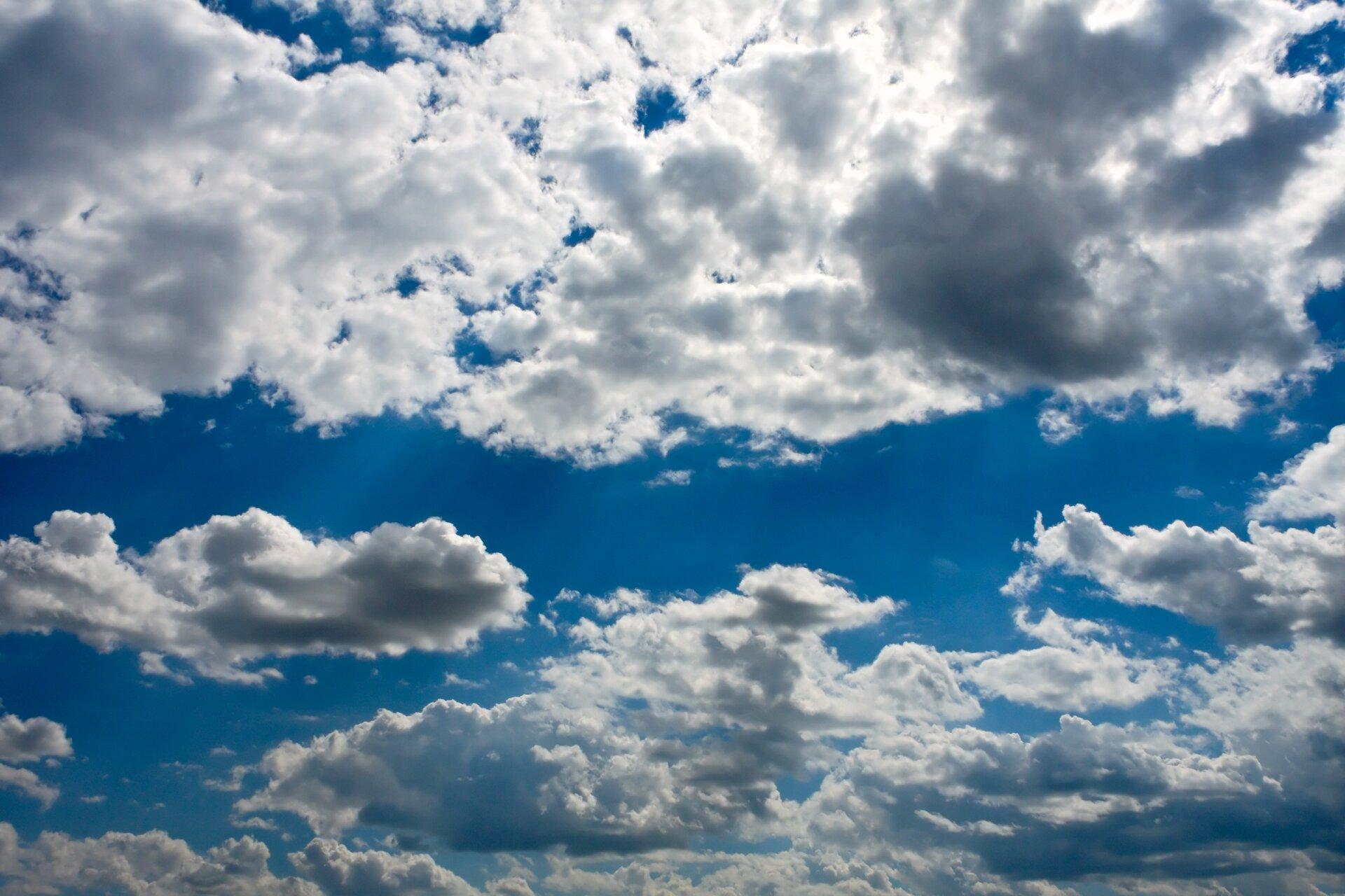 Zdjęcie przedstawia niebieskie niebo pokryte gęsto chmurami. Chmury orozmytej powierzchni. Wśrodkowej części chmury są gęste iciemne. Krawędzie chmur są nieostre ipółprzeźroczyste. Chmury wgórnej części nieba są jaśniejsze.