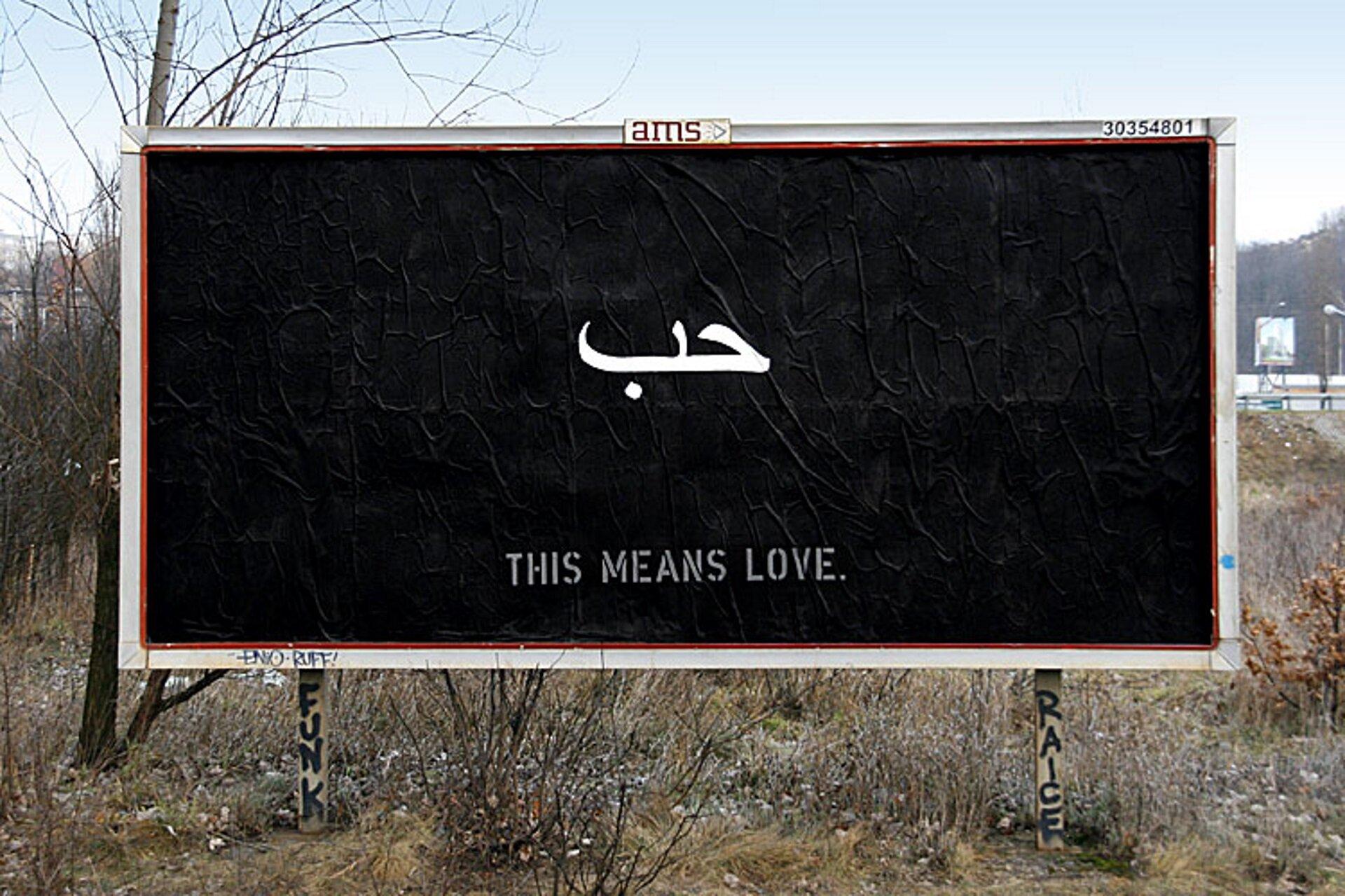 Billboard przedstawiający na czarnym tle biały napis This means love.