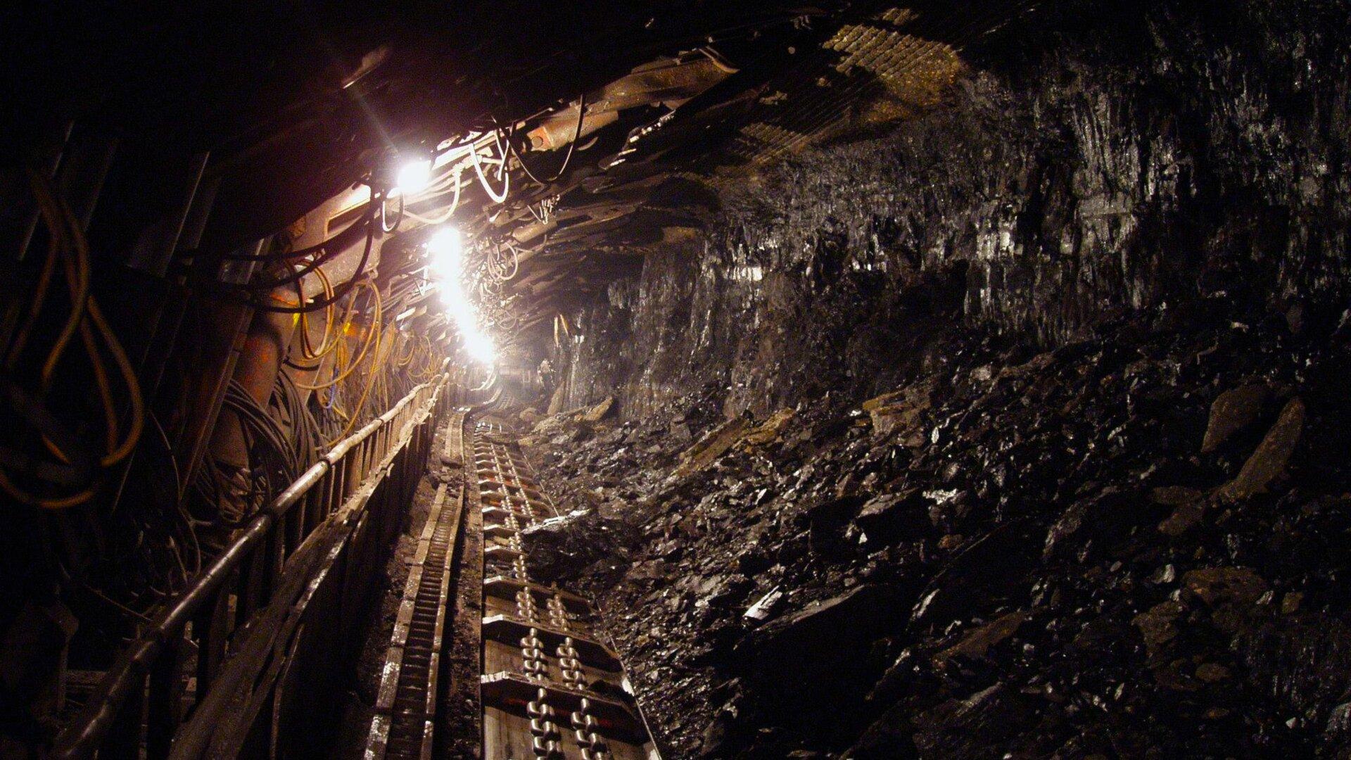 Ilustracja przedstawia zejście do kopalni. Po lewej znajdują się żółte liny zabezpieczające. Na środku zdjęcia widać trasę kolejki podziemnej oraz padające ztyłu światło.