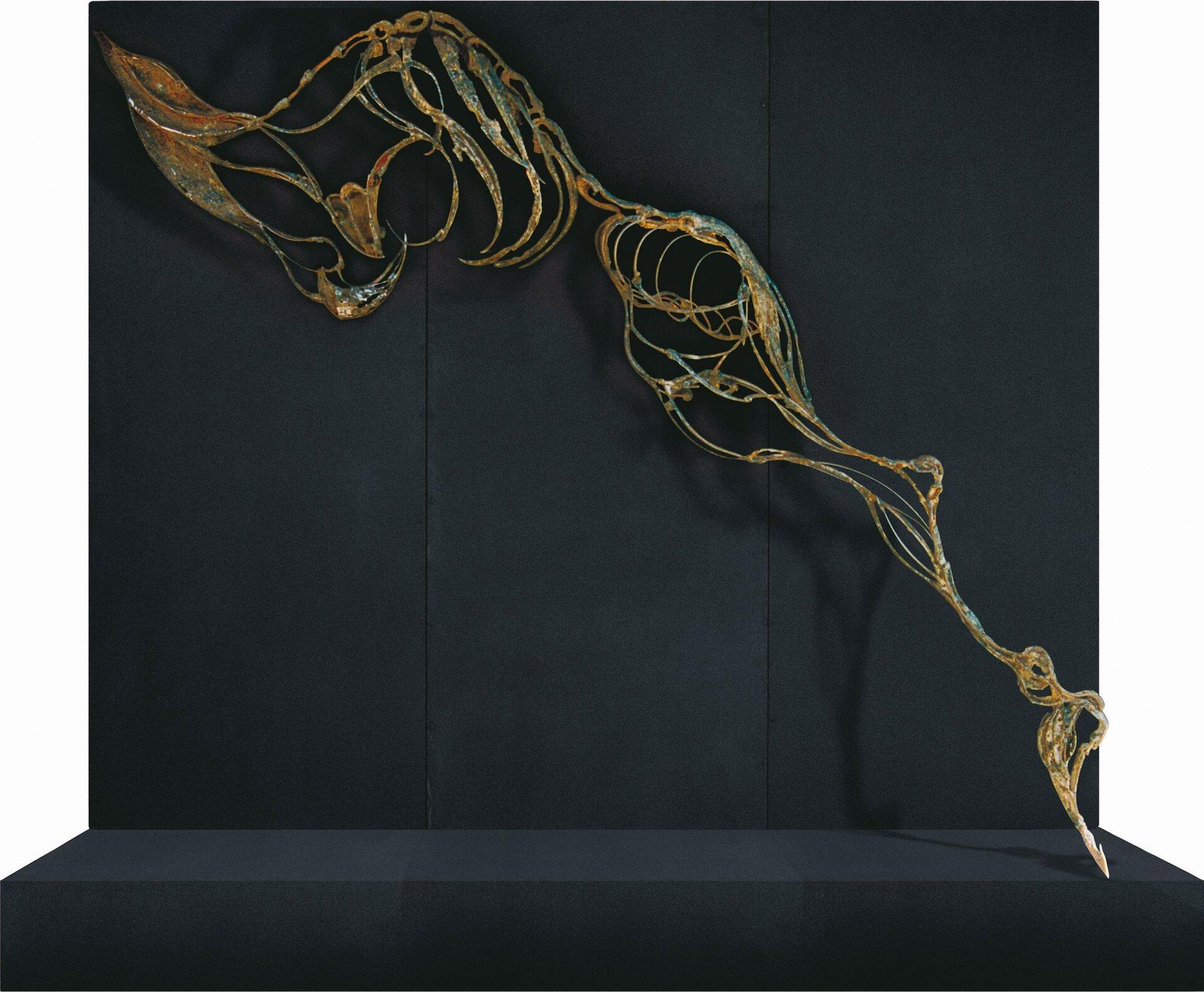 """Ilustracja przedstawia instalację zcyklu """"Upłaszczyznowienia"""" autorstwa Anny Wysockiej. Zdjęcie ukazuje rzeźbę wykonaną zmetalu, przypominającą profil ludzkiego szkieletu bez głowy irąk. Praca została skomponowana po skosie na tle grafitowego podestu. Metaliczna, złoto-brązowa, błyszcząca struktura obiektu wyłania się zciemno-szarego, matowego tła."""