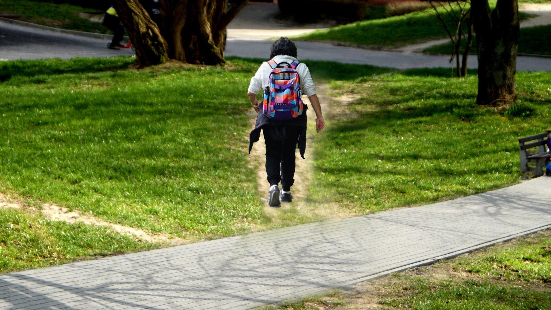 Zdjęcie przedstawia dwie osoby idące wąską boczną ścieżką.