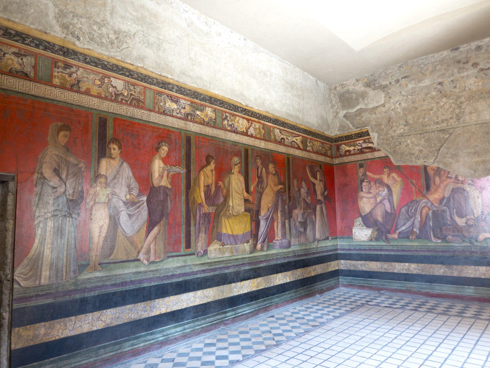 Ilustracja przedstawia wnętrze jakiegoś budynku. Prawdopodobnie jest to budynek użyteczności publicznej. Na ścianach widoczny jest fresk ukazujący ludzi wcodziennych sytuacjach.