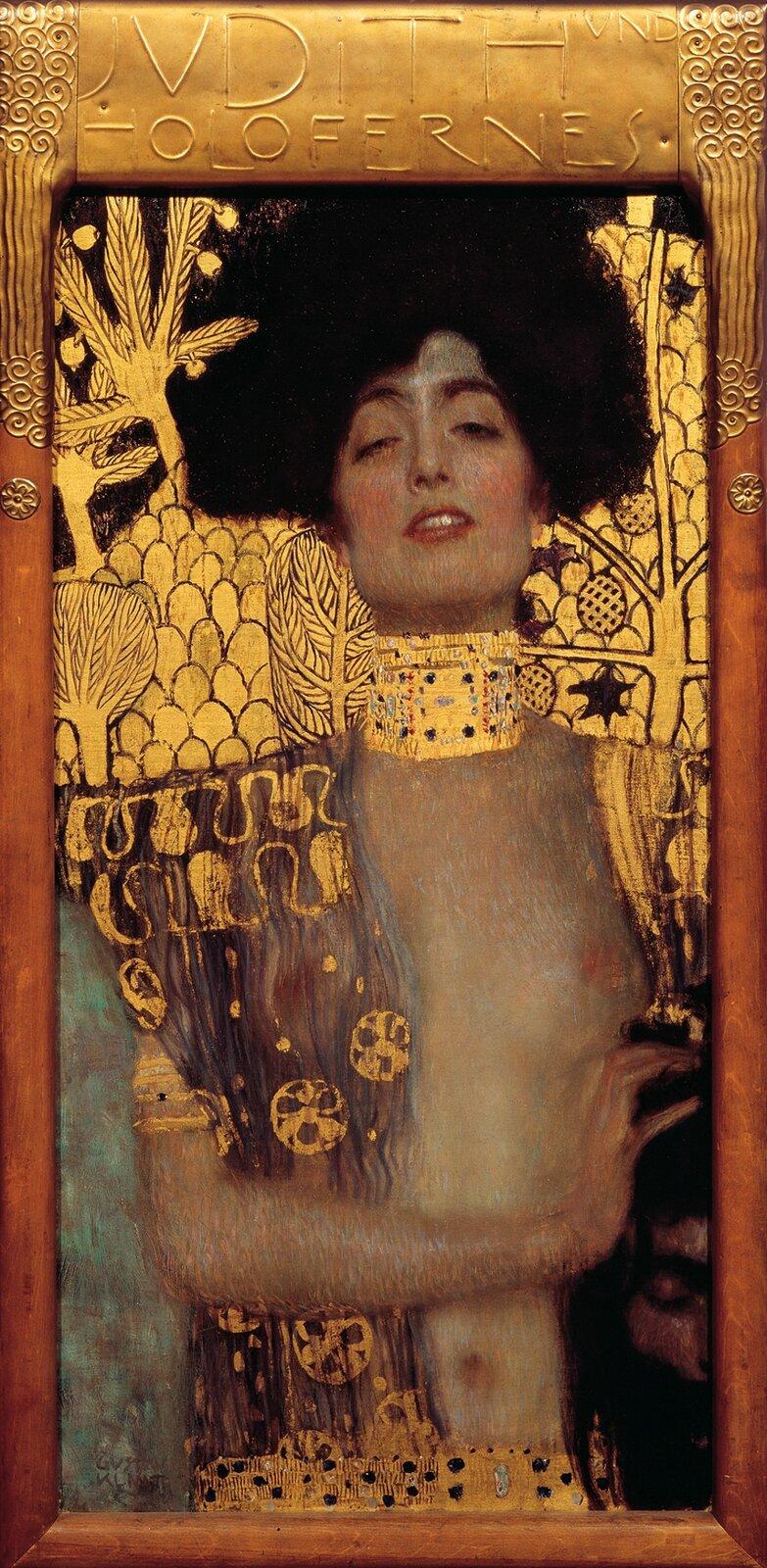 """Ilustracja przedstawia obraz """"Judyta iHolofernes I"""" autorstwa Gustawa Klimty. Obraz ukazuje kobietę ujętą od pasa wgórę. Kobieta ma na sobie szatę, która odsłania nagą pierś. Kobieta wrękach trzyma głowę mężczyzny zczarnymi włosami izarostem."""