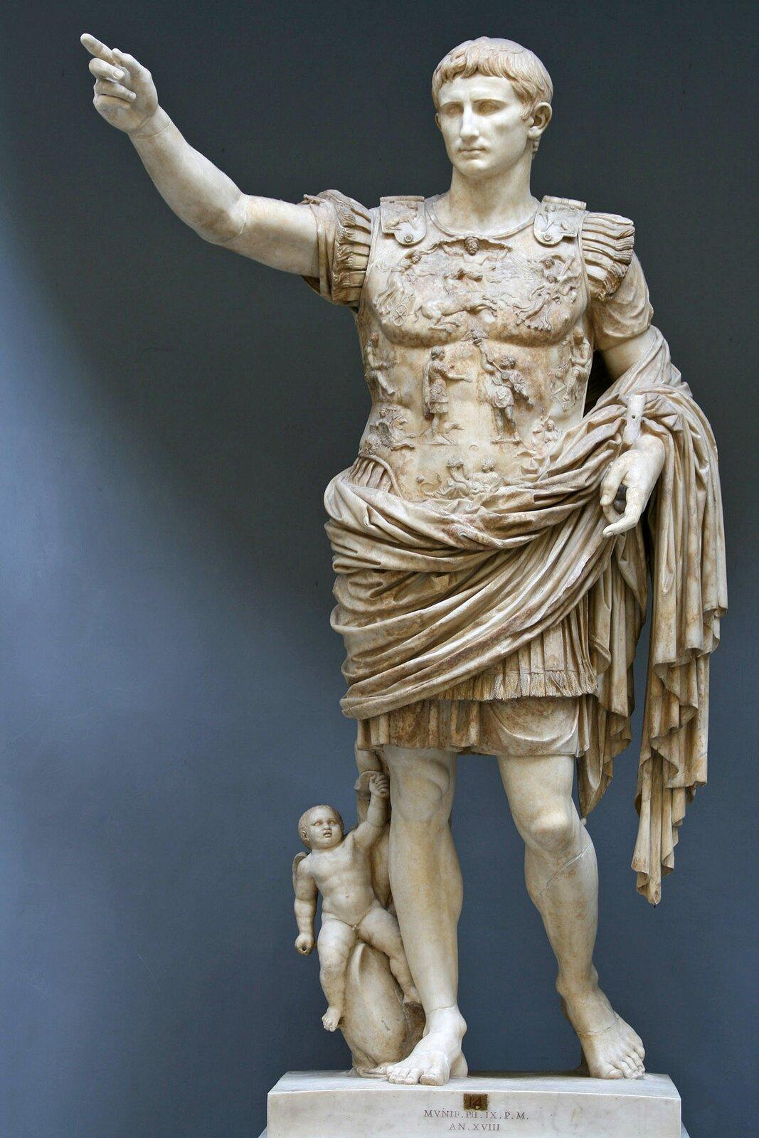 """Ilustracja przedstawia rzeźbę zatytułowaną """"August zPrima Porta"""". Ukazuje ona stojącą postać cesarza. Jest on ubrany wkrótką tunikę zzapinanym na ramionach bogato zdobionym pancerzem. Przez lewe ramię ibiodra przerzucony ma płaszcz. Wyciągnięta prawa ręka wskazuje, że władca zamierza przemówić. Rzeźba wykonana jest zgodnie zzasadą ponderacji: ciężar posągu spoczywa na prawej stopie; lewa odciążona oparta jest jedynie na palcach. Ustóp cesarza znajduje się Kupidyn na delfinie."""