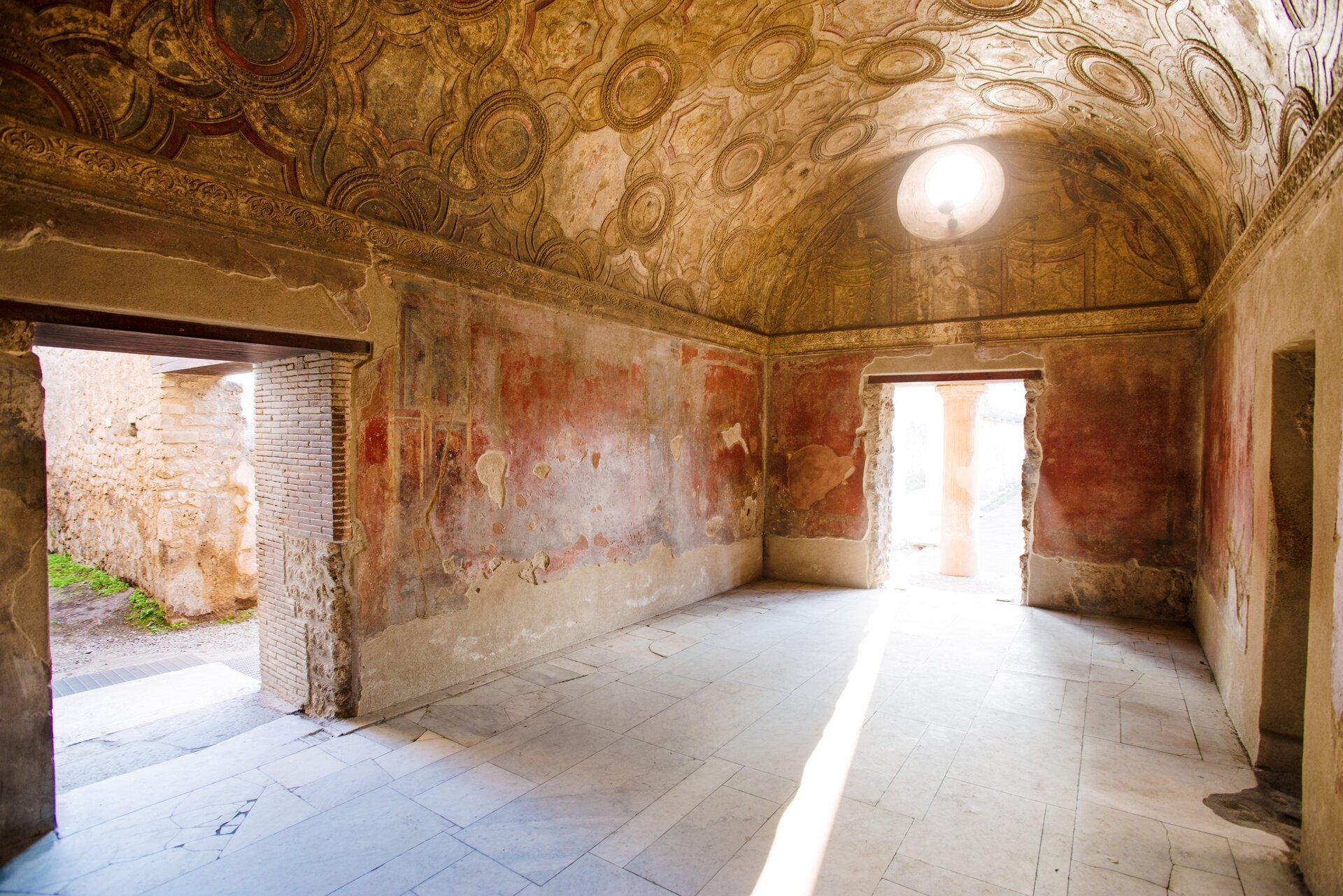 Kolorowa ilustracja przedstawia aktualny stan Łaźni Stabiana wPompejach. Na fotografii ukazano wnętrze pomieszczenia. Jest obszerne; ma trzy otwory wejściowe iłukowate sklepienie. Ściany isufit są bogato zdobione mozaiką. Podłoga wyłożona jest kamienną posadzką.