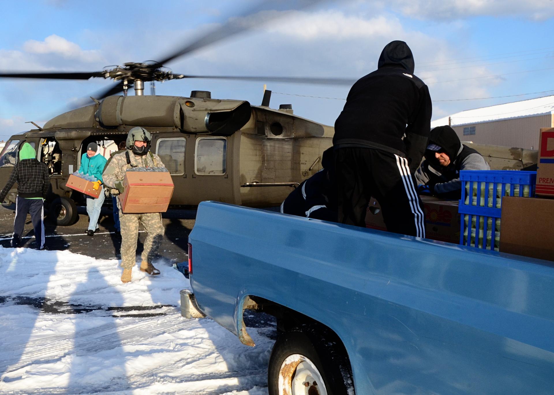 Galeria 1 składa się zdwóch zdjęć. Zdjęcie po lewej. Zimowy słoneczny dzień. Samochód zotwartą naczepą po prawej. Wtle duży wojskowy helikopter. Ratownicy ładują skrzynie zzapasami na naczepę samochodu. Żołnierz oraz kilka osób wynoszą skrzynie zzapasami zhelikoptera. Zapasy są przenoszone zhelikoptera do samochodu.