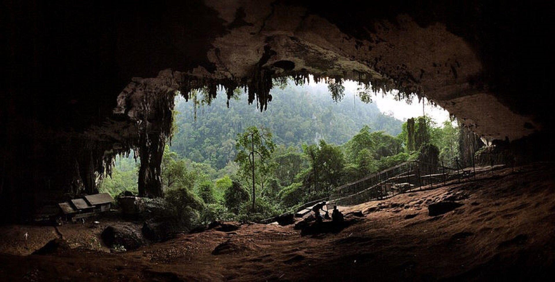 Ilustracja przedstawia jaskinię Makpela. Na ilustracji ukazane jest wnętrze jaskini, wktórej siedzą ludzie. Woddali widoczny jest las.