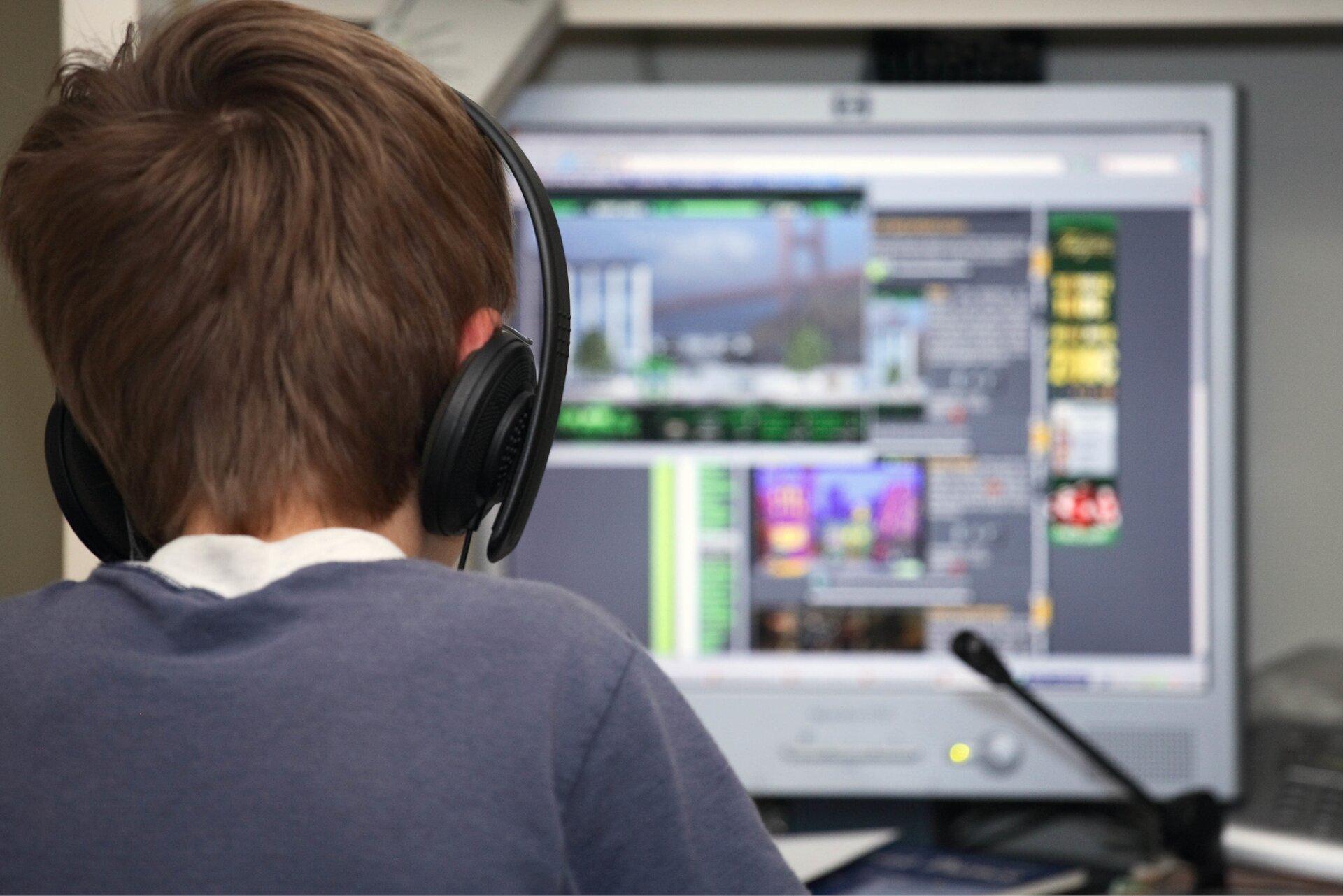 Ilustracja przedstawia uzależnienie od gier. Zdjęcie ukazuje tył młodego chłopca, siedzącego przed komputerem igrającego wgrę komputerową. Chłopiec ma na uszach założone duże słuchawki.