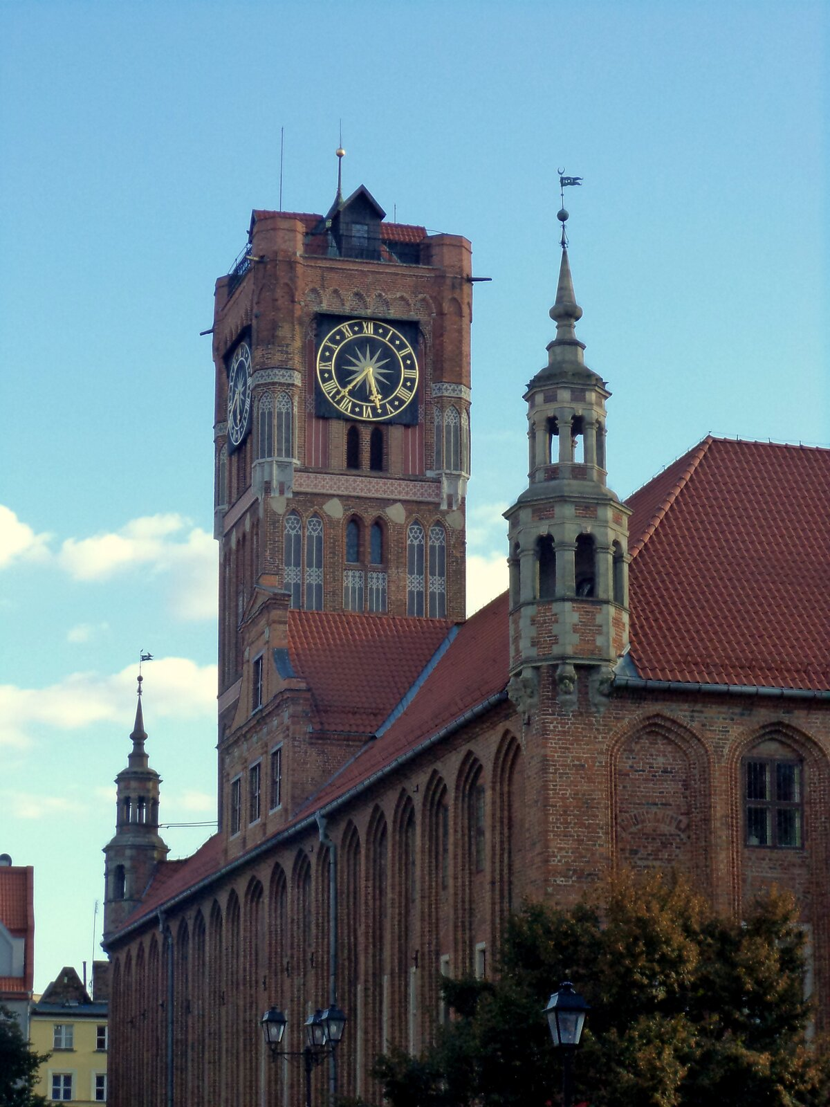 Ilustracja przedstawia Ratusz Staromiejski zXIII wieku wToruniu. Na zdjęciu ukazany jest budynek zczerwonej cegły ze spadzistym dachem zczerwoną ceramiczną dachówką, zbudowany wstylu gotyckim. Nad bryłą góruje potężna wieża zzegarem. Na ścianach budowli znajdują się charakterystyczne dla gotyku wnęki zakończone ostrym łukiem. Naroża zwieńczone są nadwieszonymi wieżyczkami, które dobudowano na początku XVII wieku.