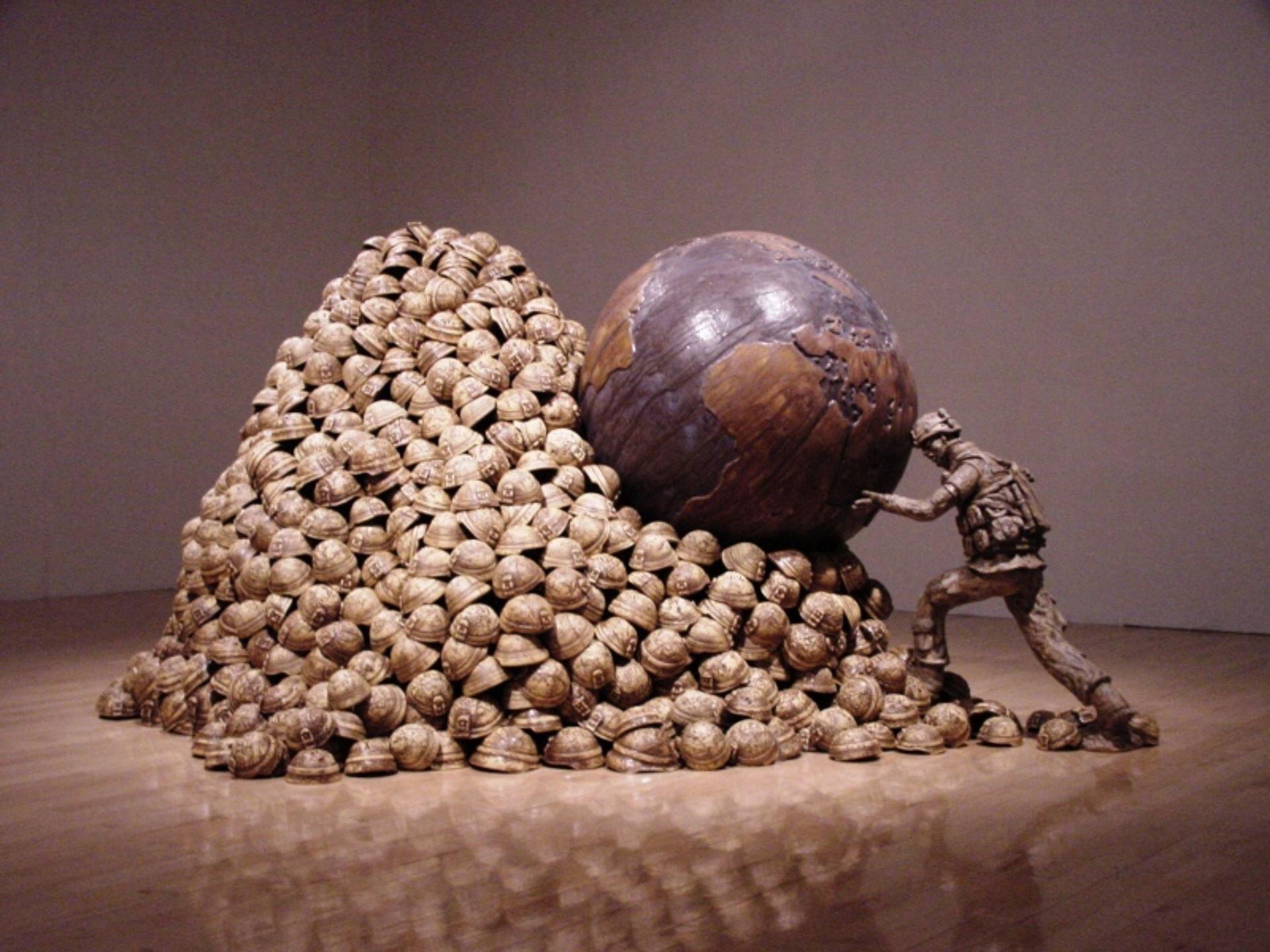 """Ilustracja przedstawia ceramiczną rzeźbę Stevena M. Allena pt. """"Syzyf"""". Ukazuje ona żołnierza pchającego kamień wformie kuli ziemskiej pod górę zrobioną zhełmów wojskowych. Podpiera on kulę głową irękoma."""