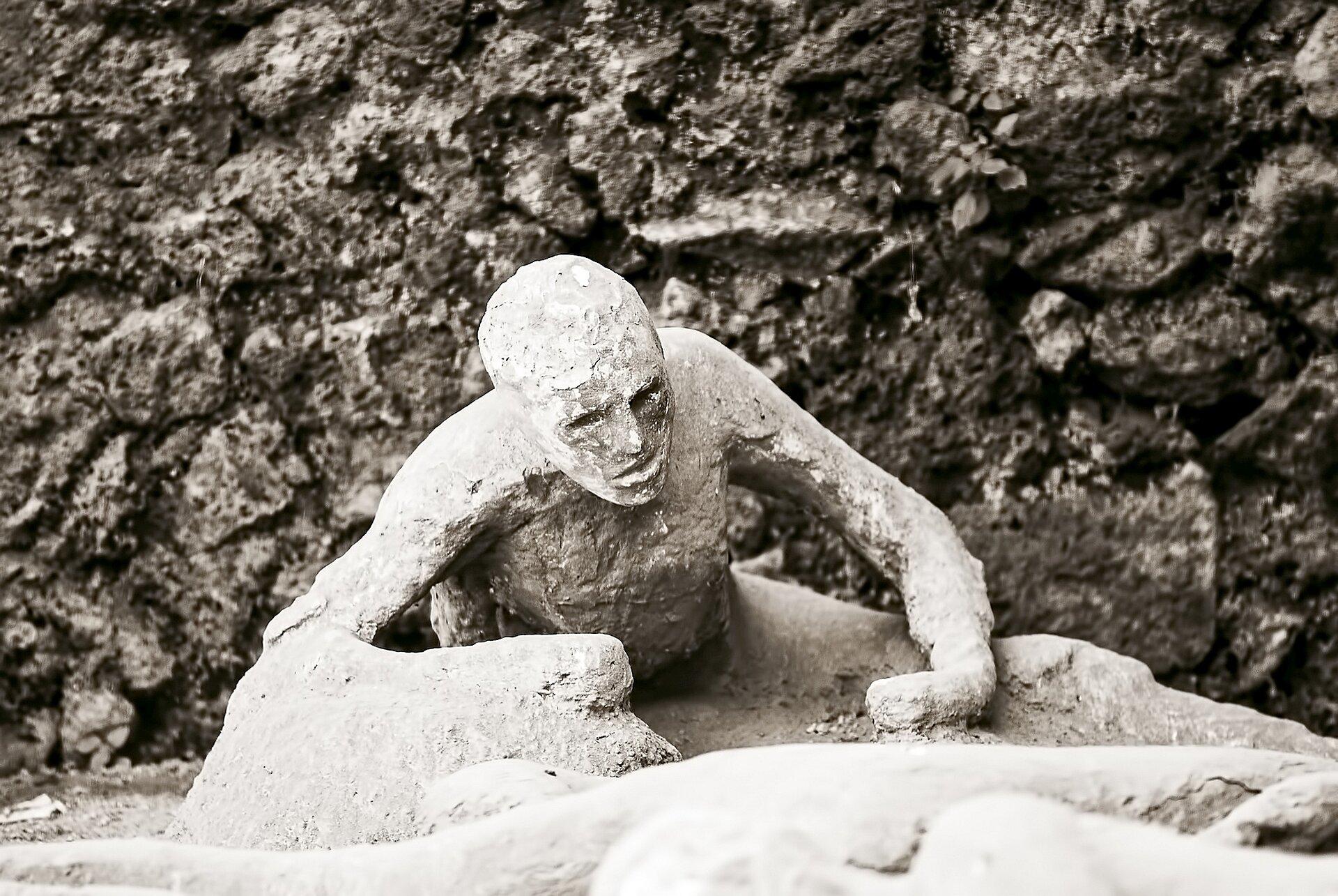 Czarnobiała ilustracja przedstawia odlew gipsowy ciała ofiary wybuchu Wezuwiusza. Ukazany jest człowiek, który odpycha się rękami od podłoża, próbując wstać. Głowę podnosi do góry. Widoczne są rysy jego twarzy. Tło stanowi ciemna ściana przypominająca skałę wulkaniczną.