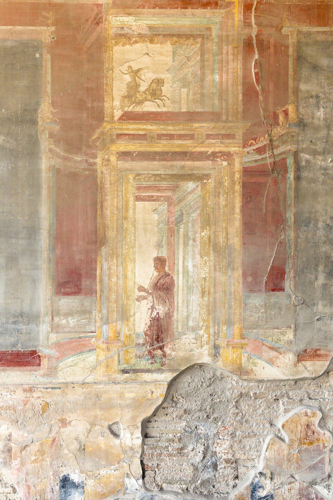 Kolorowa ilustracja przedstawia fresk ukazujący mężczyznę stojącego wdrzwiach. Ubrany jest wczerwoną szatę, stoi bokiem, wyciąga przed siebie ręce. Drzwi mają żółtą framugę; namalowane zostały na czerwonej ścianie. Nad drzwiami ukazane jest malowidło przedstawiające kobietę jadącą wpowozie zaprzężonym wdwa konie.