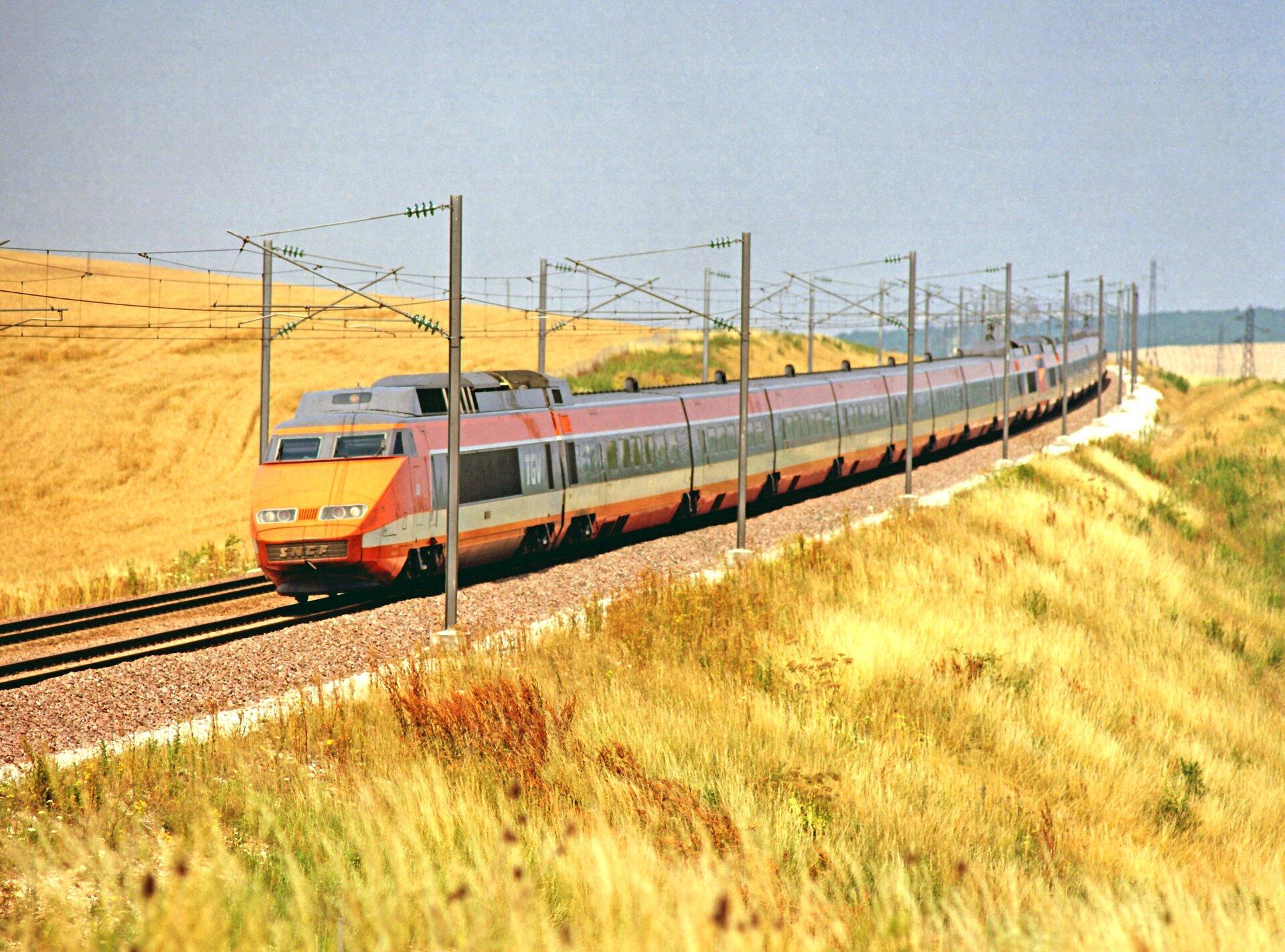 Zdjęcie przedstawia pociąg jadący po torach. Pociąg pomarańczowo-czerwony. Wtle błękitne niebo ipola uprawne. Pociąg zdaje się poruszać po łuku.