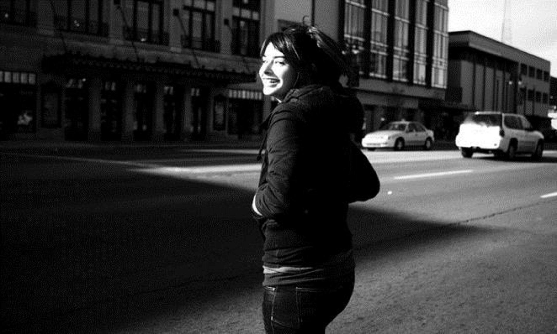Czarnobiała fotografia nieznanego autora przedstawia kobietę pozującą na tle budynków wcentrum miasta. Kobieta ma jasną karnację, długie ciemne włosy. Ubrana jest wciemną kurtkę oraz dżinsowe spodnie. Wtle widoczne są jadące białe auta, oraz budynki stojące woddali.