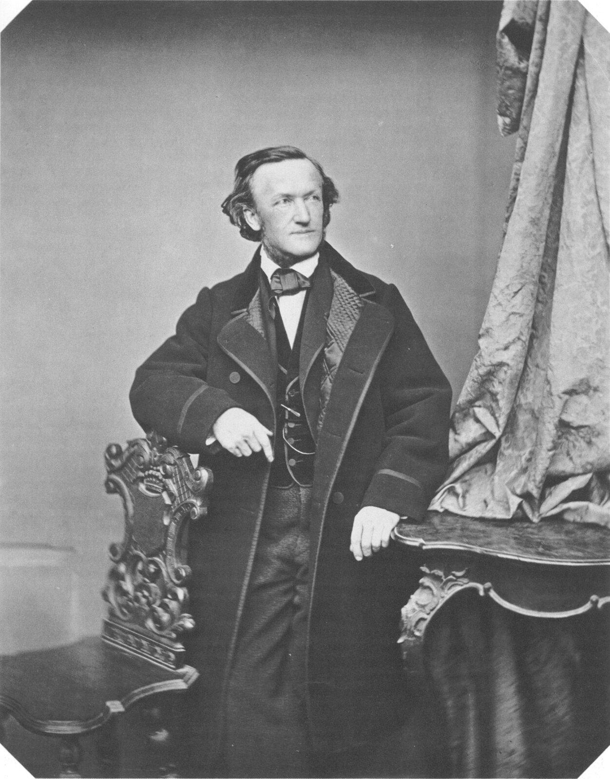 Fotografia przedstawia portret Ryszarda Wagnera. Mężczyzna oparty jest ooparcie krzesła, wyraz twarzy ma spokojny. Ubrany jest wgarnitur iciemny, gruby płaszcz.