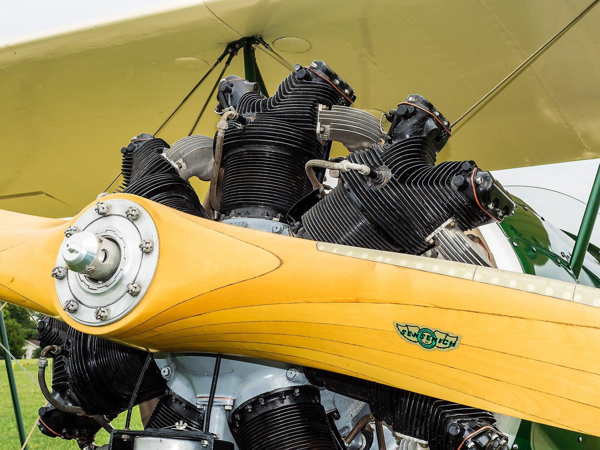 Zdjęcie przedstawia wzbliżeniu silnik samolotu dwupłatowego icentralną część śmigła. Śmigło żółte, drewniane, silnik wkonstrukcji gwiazdowej, zczarnymi cylindrami rozmieszczonymi koncentrycznie wokół centralnego wału korbowego wsrebrnej oprawie. Na cylindrach wyraźne ożebrowanie służące lepszemu odprowadzaniu ciepła. Ztyłu część kadłuba samolotu wkolorze zielonym oraz fragment górnego skrzydła wkolorze żółtym. Wlewym dolnym narożniku kadru wtle trawa idrzewa.