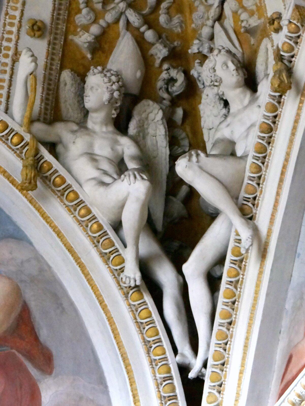 Ilustracja przedstawia detal rzeźbiarski zkaplicy Theodoli wbazylice Santa Maria del Popolo autorstwa Giulio Mazzoni. Na zdjęciu znajdują się dwie rzeźby siedzących nagich aniołów. Postacie wpisane są warchitekturę sklepienia. Umieszczono je na styku zdobionych żółtym ornamentem wolich oczu łuków. Nogi rzeźb lekko wystają poza ich krawędzie. Głowy okalają drobne loczki włosów. Anioł po lewej stronie spogląda wlewo, natomiast anioł po prawej wprawo. Za postaciami, na żółto malowanym sklepieniu znajdują się drobne białe płaskorzeźby zmotywami roślinnymi iinsygniami władzy kościelnej.