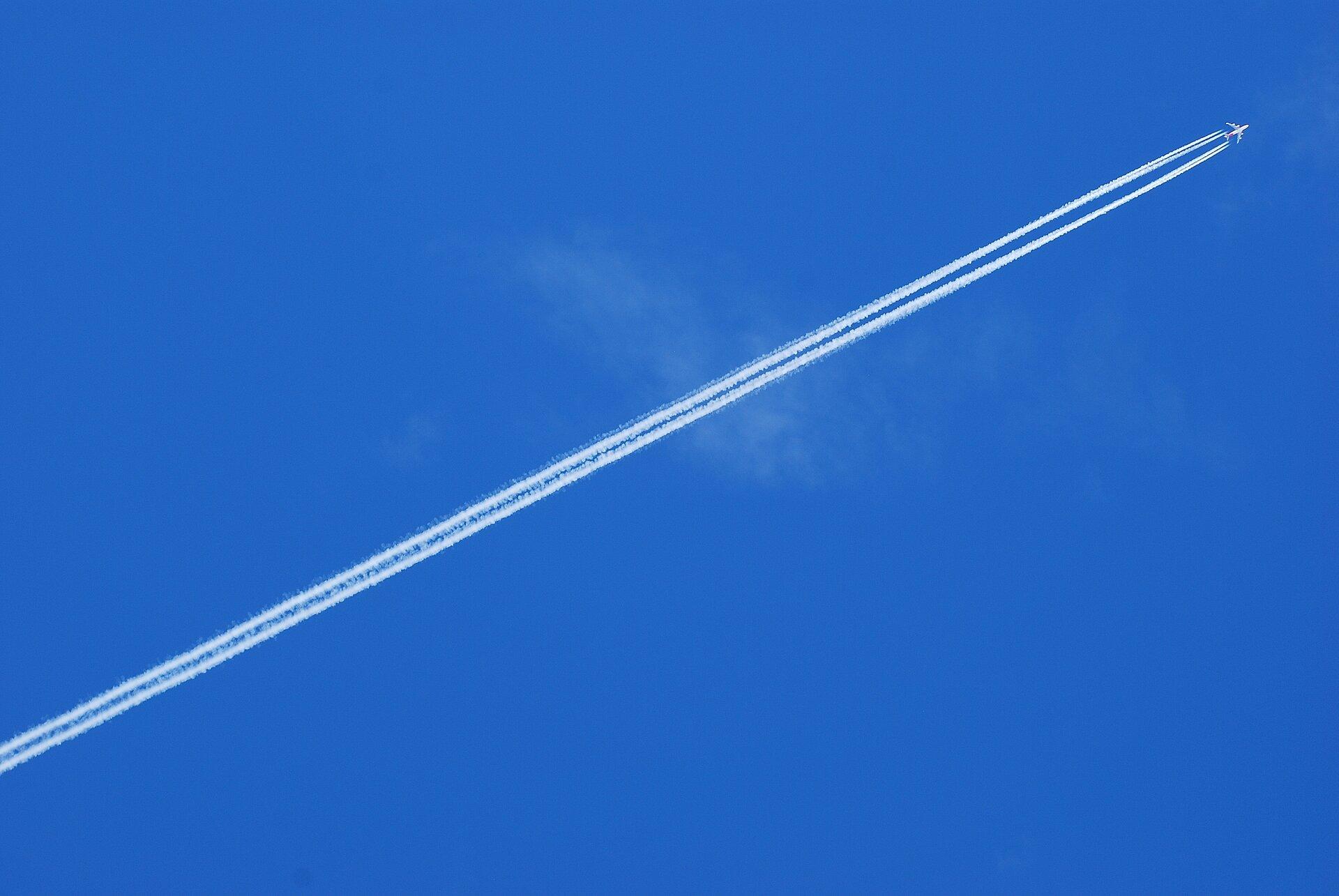 Zdjęcie przedstawia samolot na tle nieba. Niebo intensywnie niebieskie. Samolot widoczny zoddali. Samolot bały, widok od dołu. Za samolotem dwie długie, białe smugi.