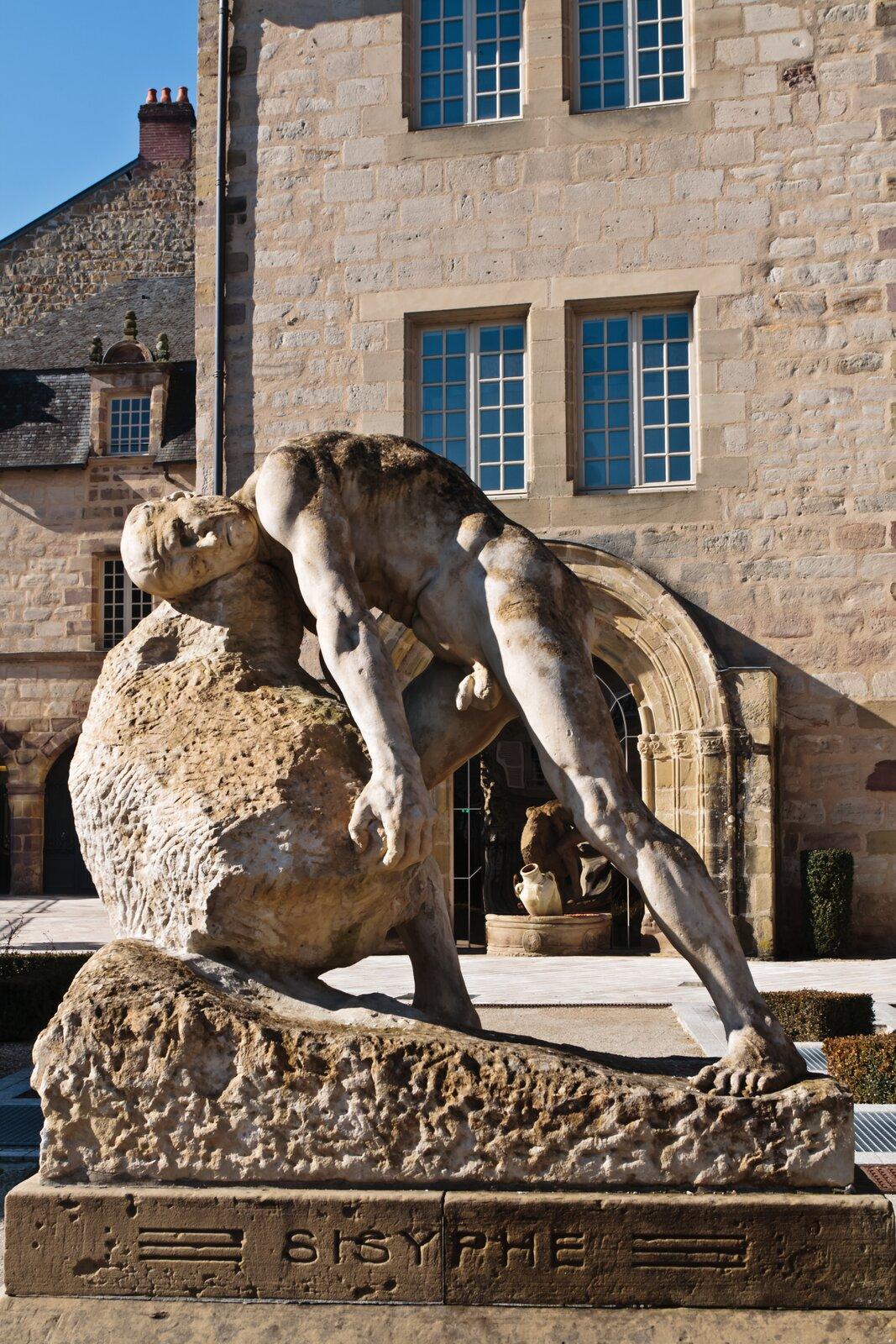 Ilustracja przedstawia rzeźbę Syzyfa wakcie, toczącego duży kamień. Król Koryntu głowę ma położoną na kamieniu. Próbuje od dołu podnieść głaz. Postać ma napięte mięśnie. Wtle za rzeźbą znajdują się budynki.