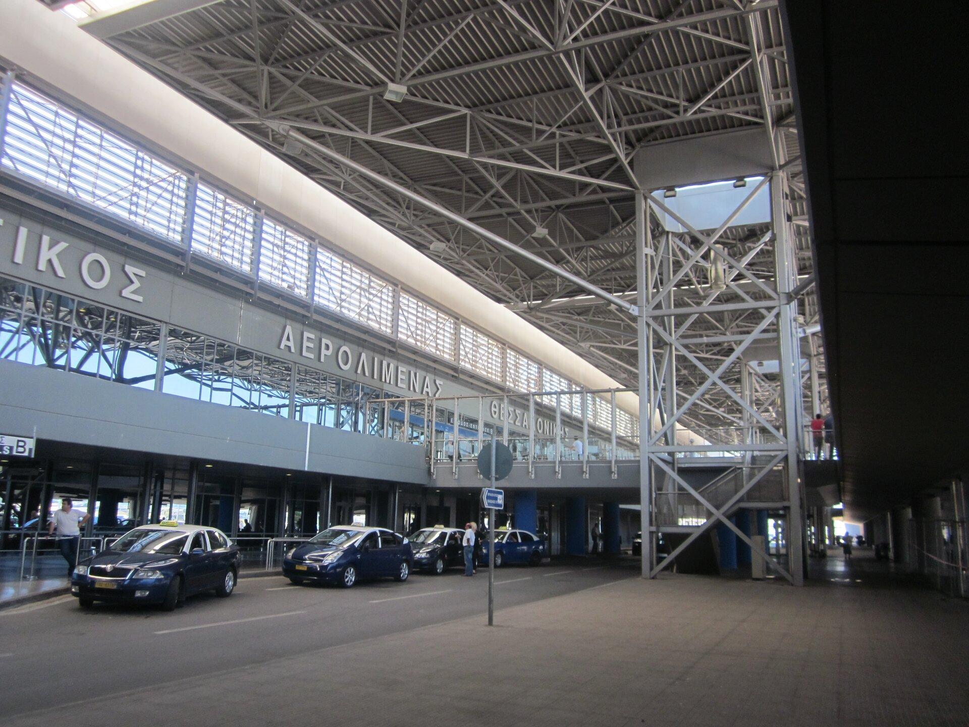 Hala lotniska, napisy walfabecie greckim. Przed halą taksówki.