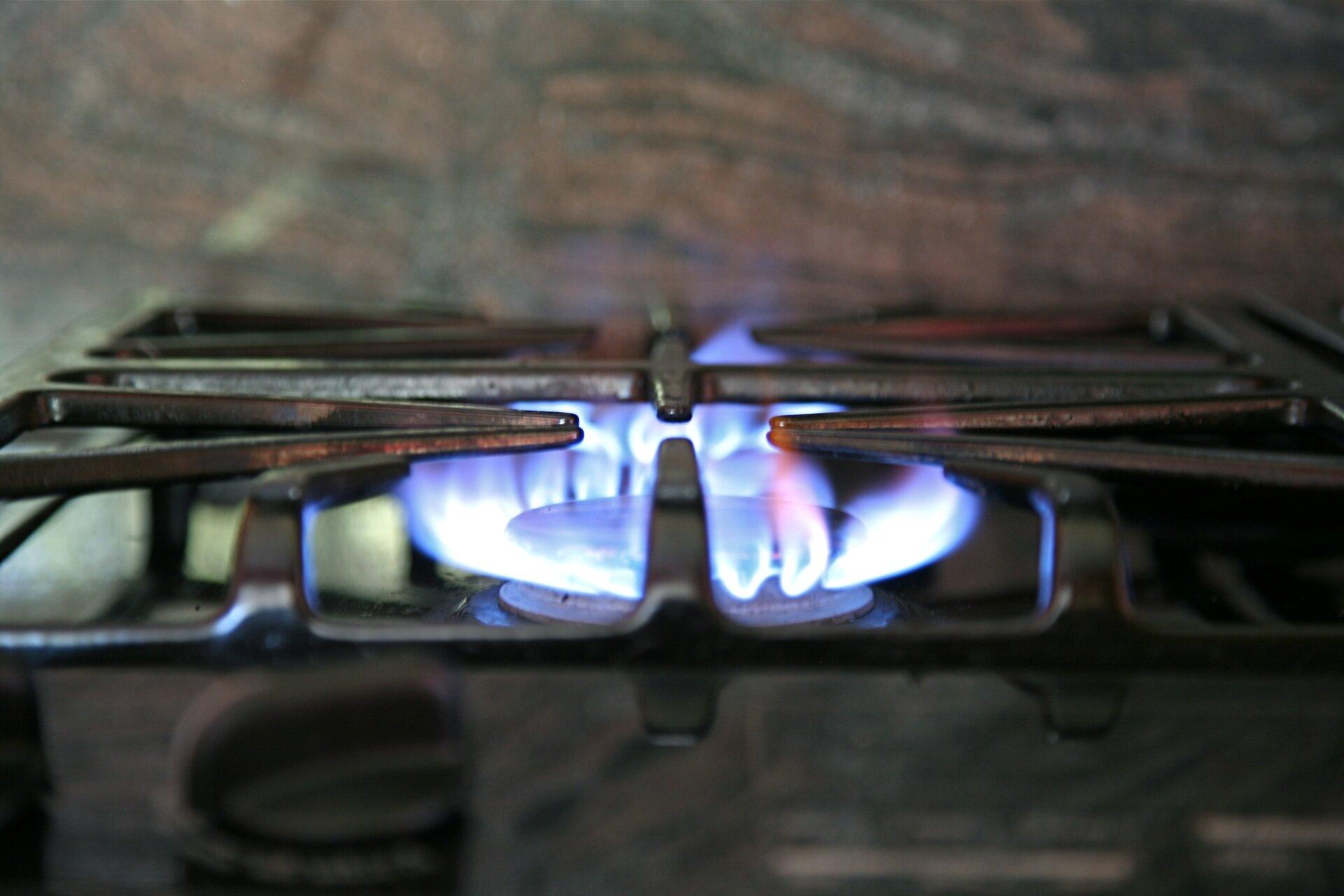 Kolorowe zdjęcie przedstawia zapalony palnik gazowy na piecu kuchennym. Wokół palnika wkształcie koła niebiesko-białe płomienie palącego się gazu. Nad palnikiem czarny, żelazny ruszt.