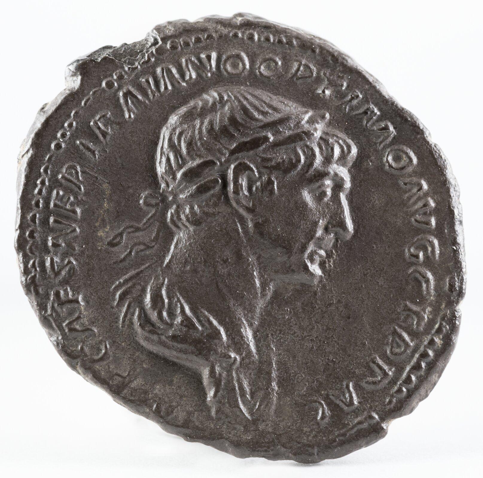Fotografia nieznanego autora przedstawia monetę zwizerunkiem Trajana. Cesarz pokazany jest zprofilu. Wokół niego znajdują się łacińskie inskrypcje.