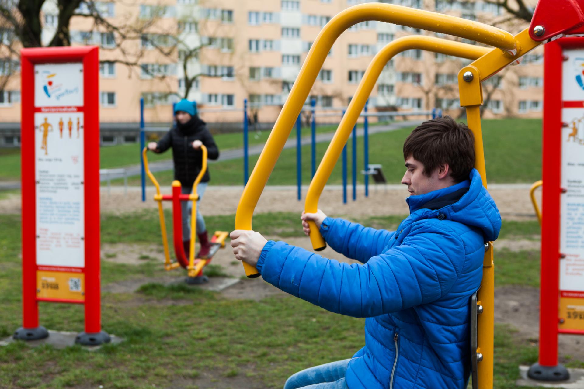 Fotografia przedstawia dwie osoby, ćwiczące na siłowni zewnętrznej przed blokiem. Zprawej mężczyzna wniebieskiej kurtce siedzi na urządzeniu, trzymając dwie żółte rury. Tablice wczerwonych metalowych ramach zawierają instrukcję ćwiczenia na przyrządach. Kobieta ztyłu wkurtce iniebieskiej czapce stoi na żółto – czerwonym steperze, trzymając jego rączki.