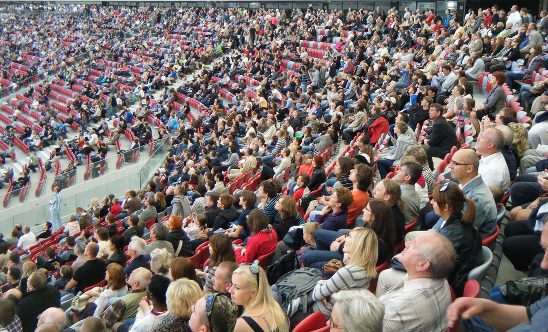 Na zdjęciu ludzie wróżnym wieku siedzący na widowni dużej hali lub stadionu.