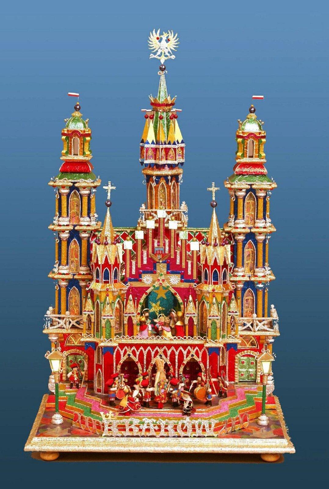 Na zdjęciu szopka bożonarodzeniowa, pochodząca zKrakowa. Szopka podobna jest zdo kościoła zwieżami. Na podwyższeniu, wrodzaju balkonu święta Rodzina. Ustóp budowli figurki krakowiaków ikrakowianek.