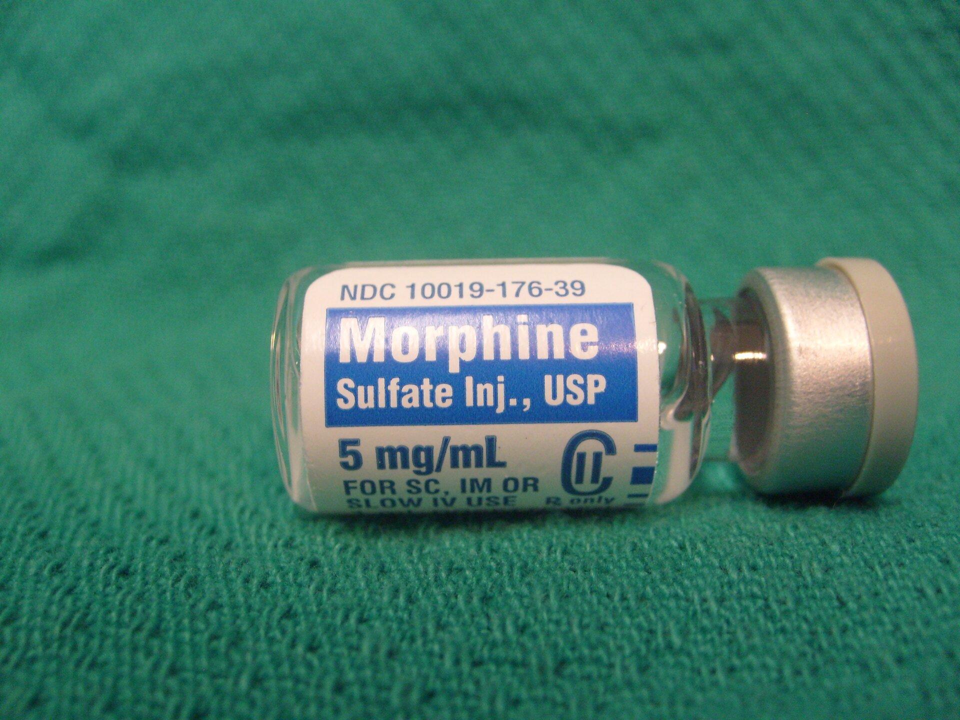 Fotografia przedstawia leżącą na boku fiolkę morfiny. Fiolka jest szklana, zmetalowo-gumowym korkiem. Etykieta informuje ozawartości. Morfina jest skutecznym środkiem uśmierzającym ból.