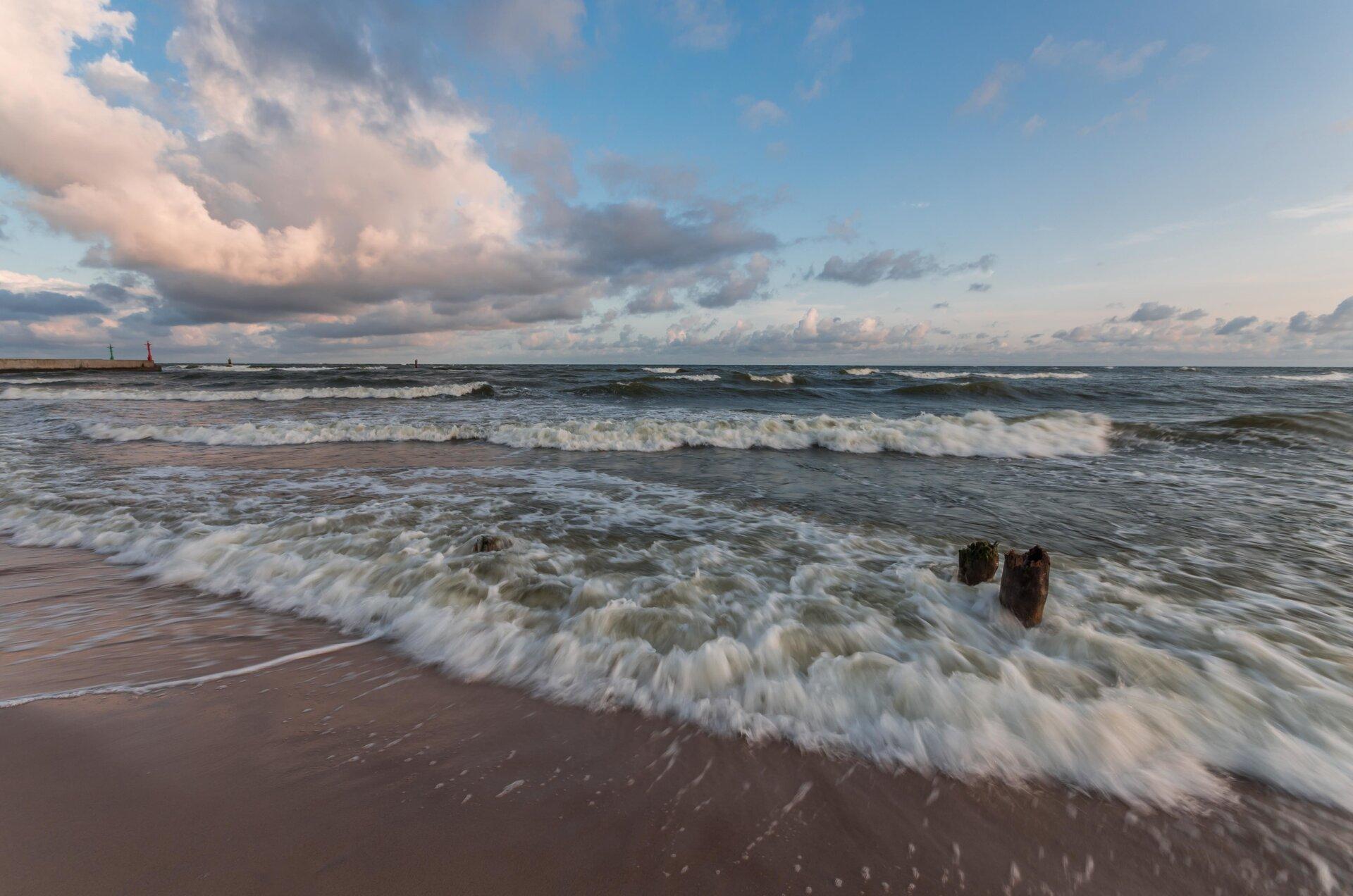 Ilustracja przedstawia wzburzone morze. Widoczny jest także fragment plaży. Na niebie kłębią się białe chmury.