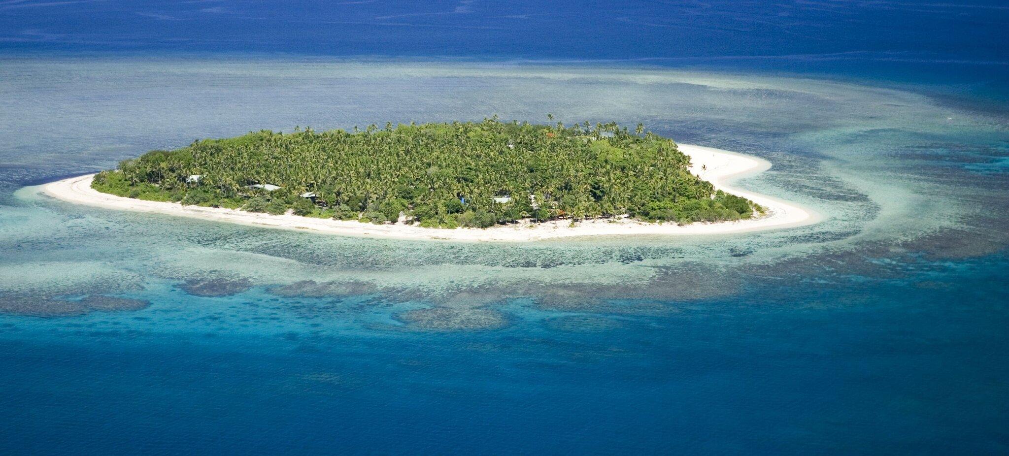 Porośnięta zielonymi zaroślami idrzewami wyspa otoczona ze wszystkich stron niebieską wodą. Pomiędzy zaroślami, awodą jest jasnożółta, prawie biała plaża.