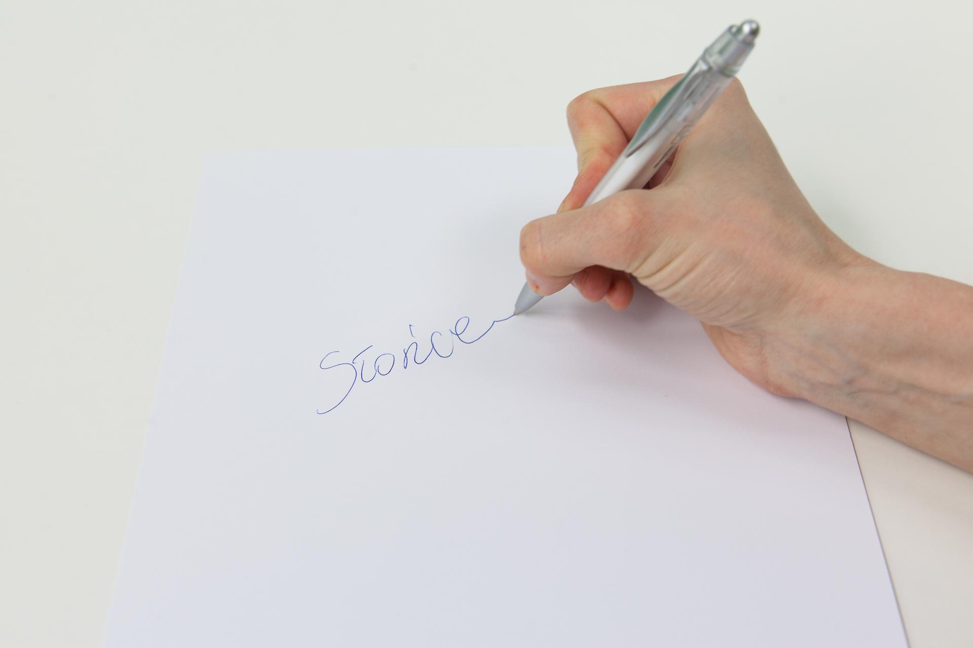Zdjęcie dłoni zdługopisem piszącym po kartce